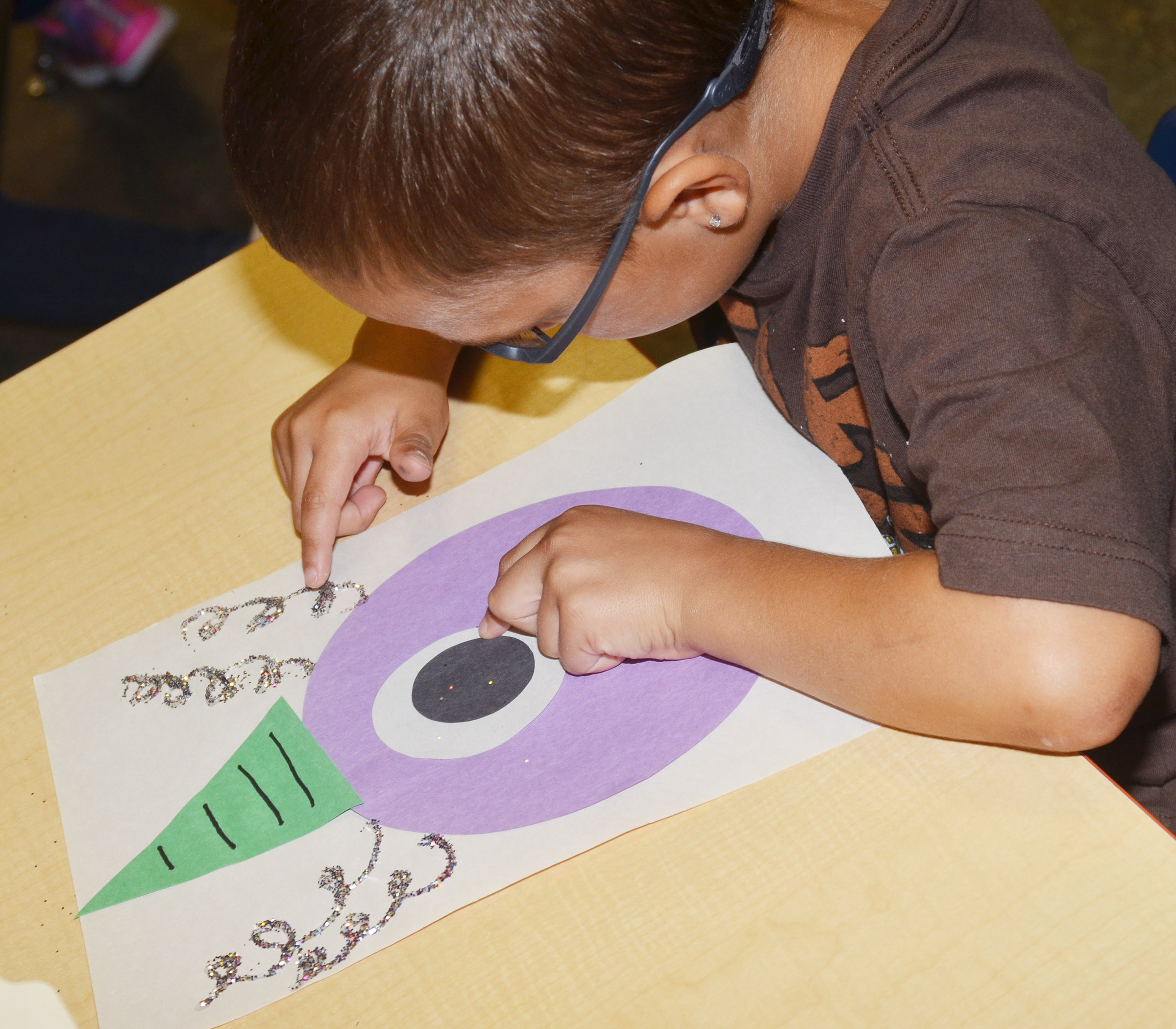 CES kindergartener Chanler Mann touches the glitter on his purple people eater.