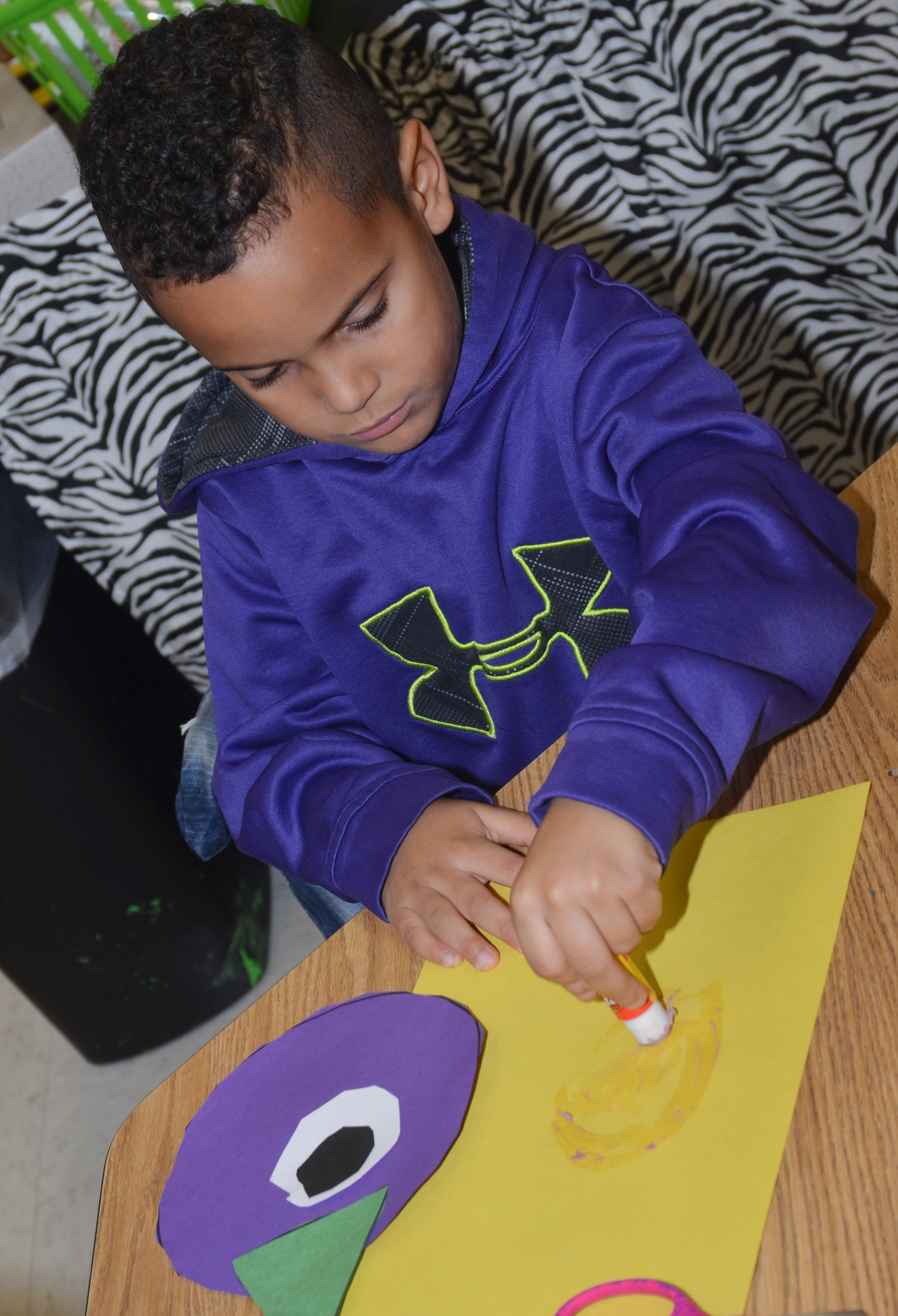 CES kindergartener Kingston Cowherd glues his purple people eater onto a piece of construction paper.