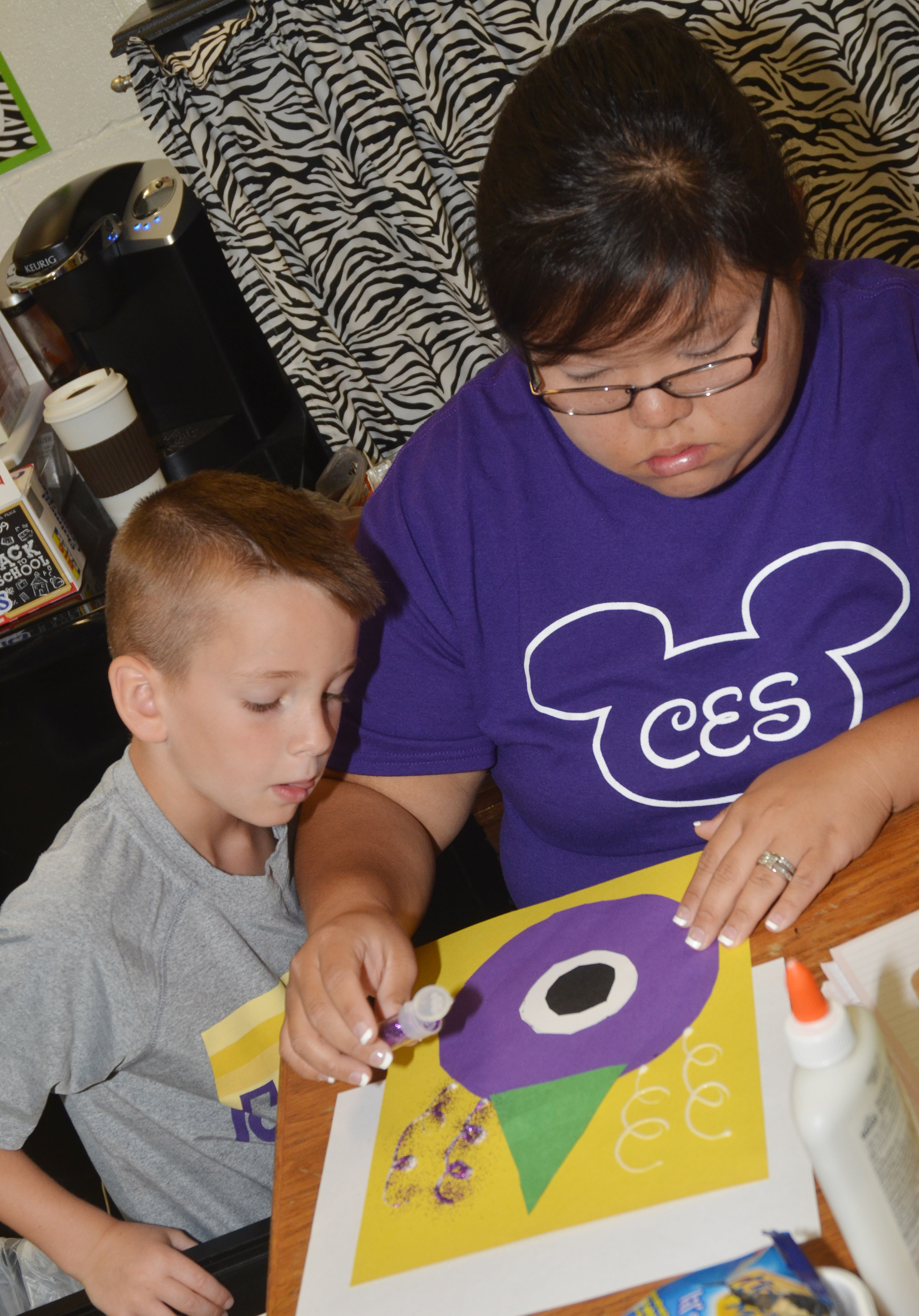 CES kindergarten assistant Brittany Johnson adds glitter to Cash Davis's purple people eater.