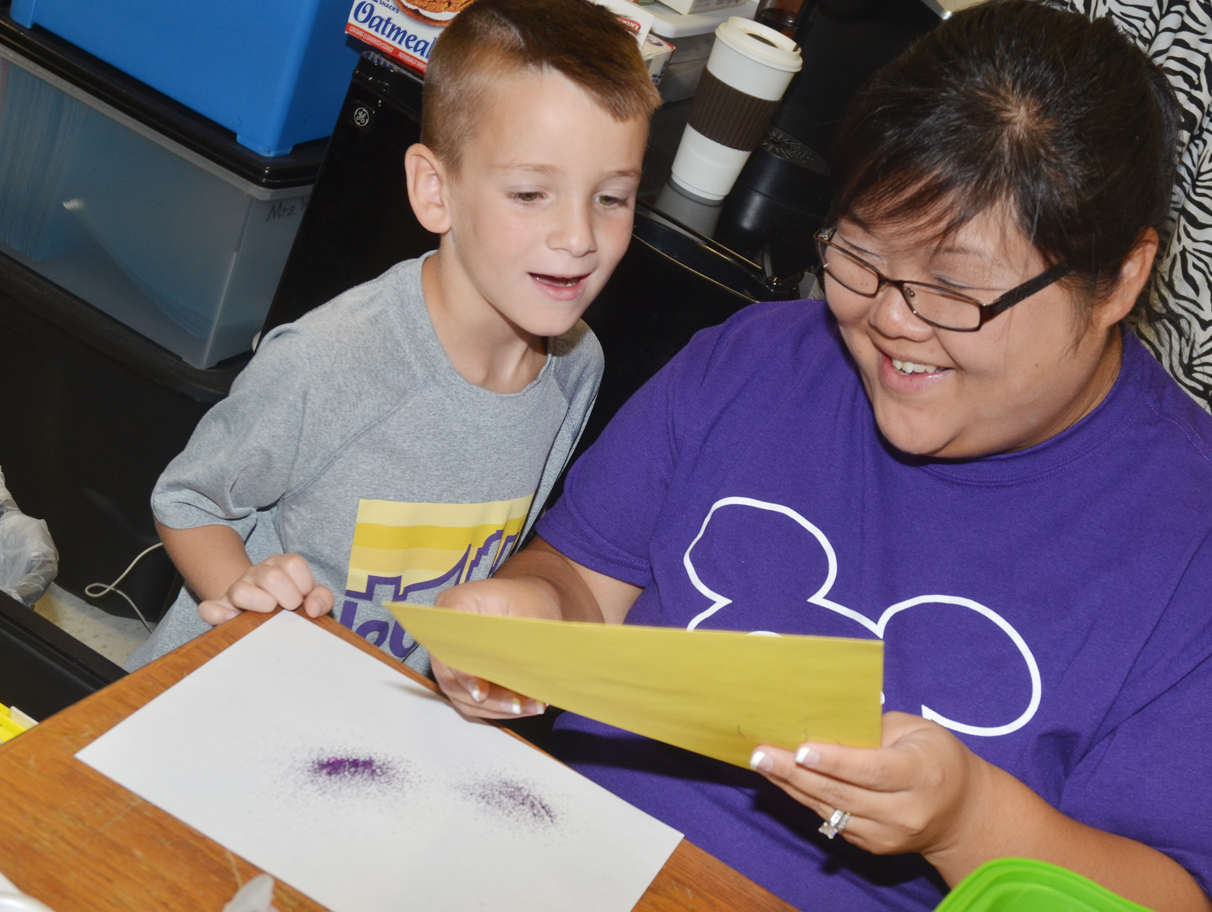 CES kindergarten assistant Brittany Johnson shows Cash Davis his finished purple people eater.