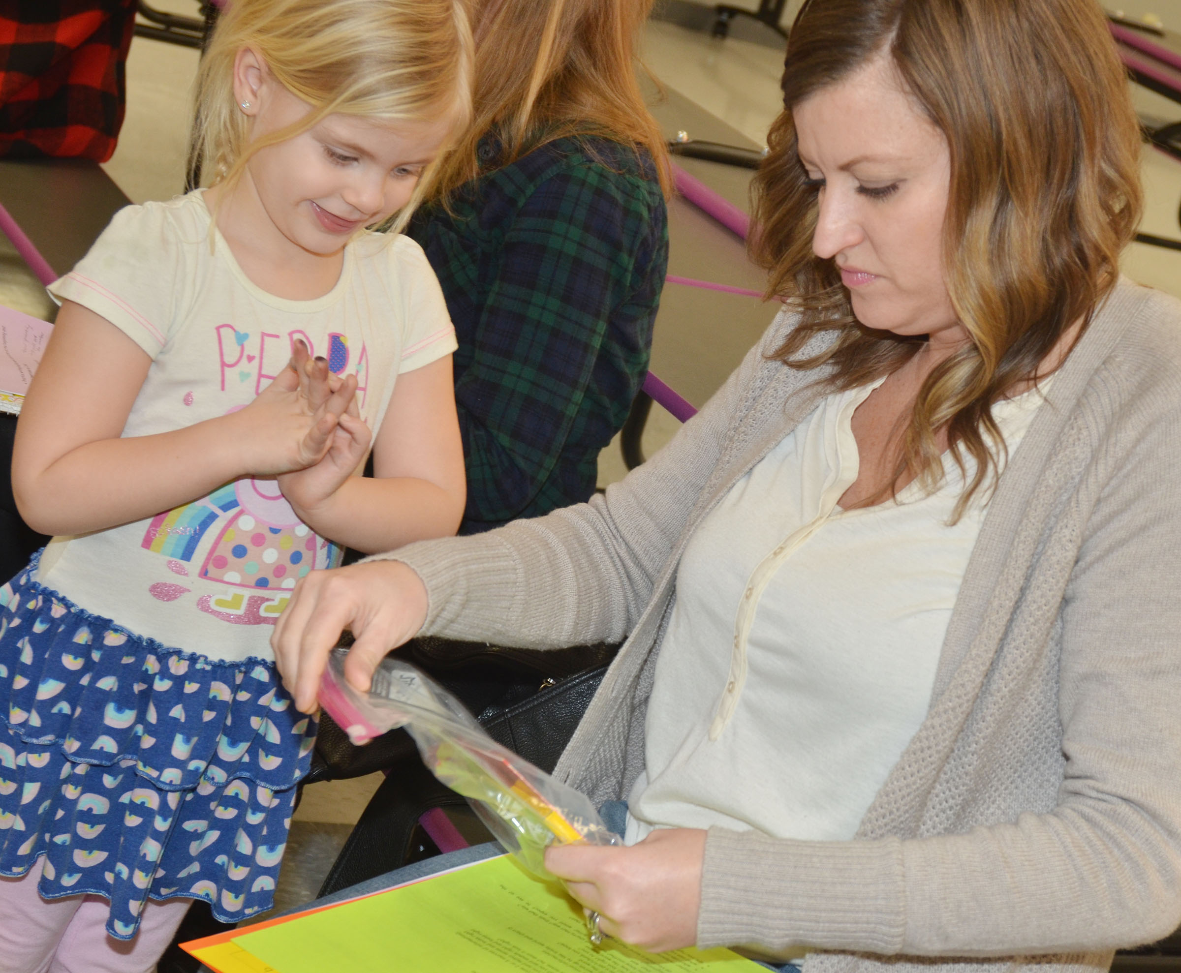 CES teacher Ashlee Petett shows her daughter, Remi, some books and crayons they received at the kindergarten readiness event. Remi will start kindergarten next school year.