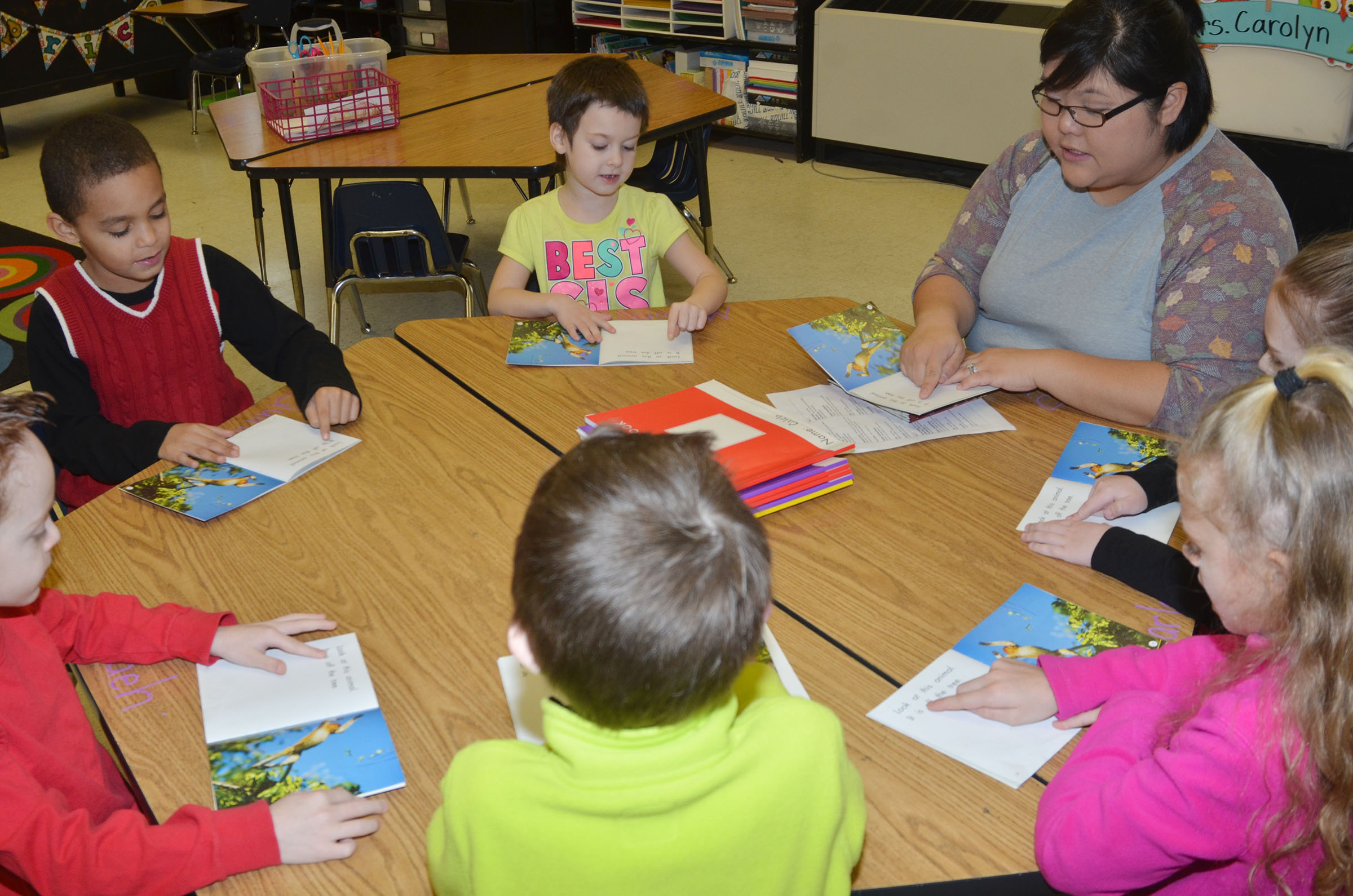 CES kindergarten assistant Brittany Johnson reads with students in her reading group.