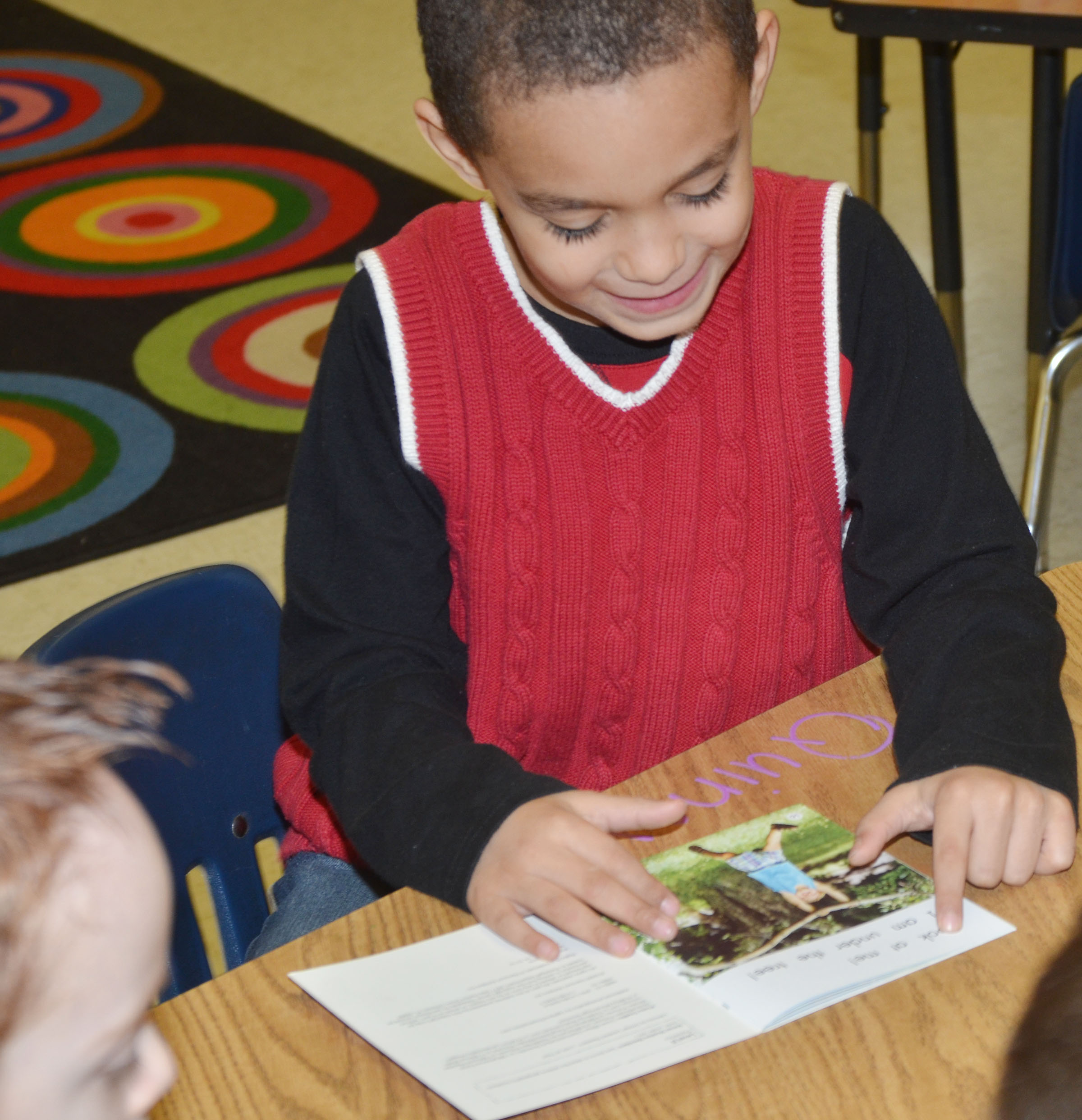 CES kindergartener Quincy Travis reads with his classmates during reading group.