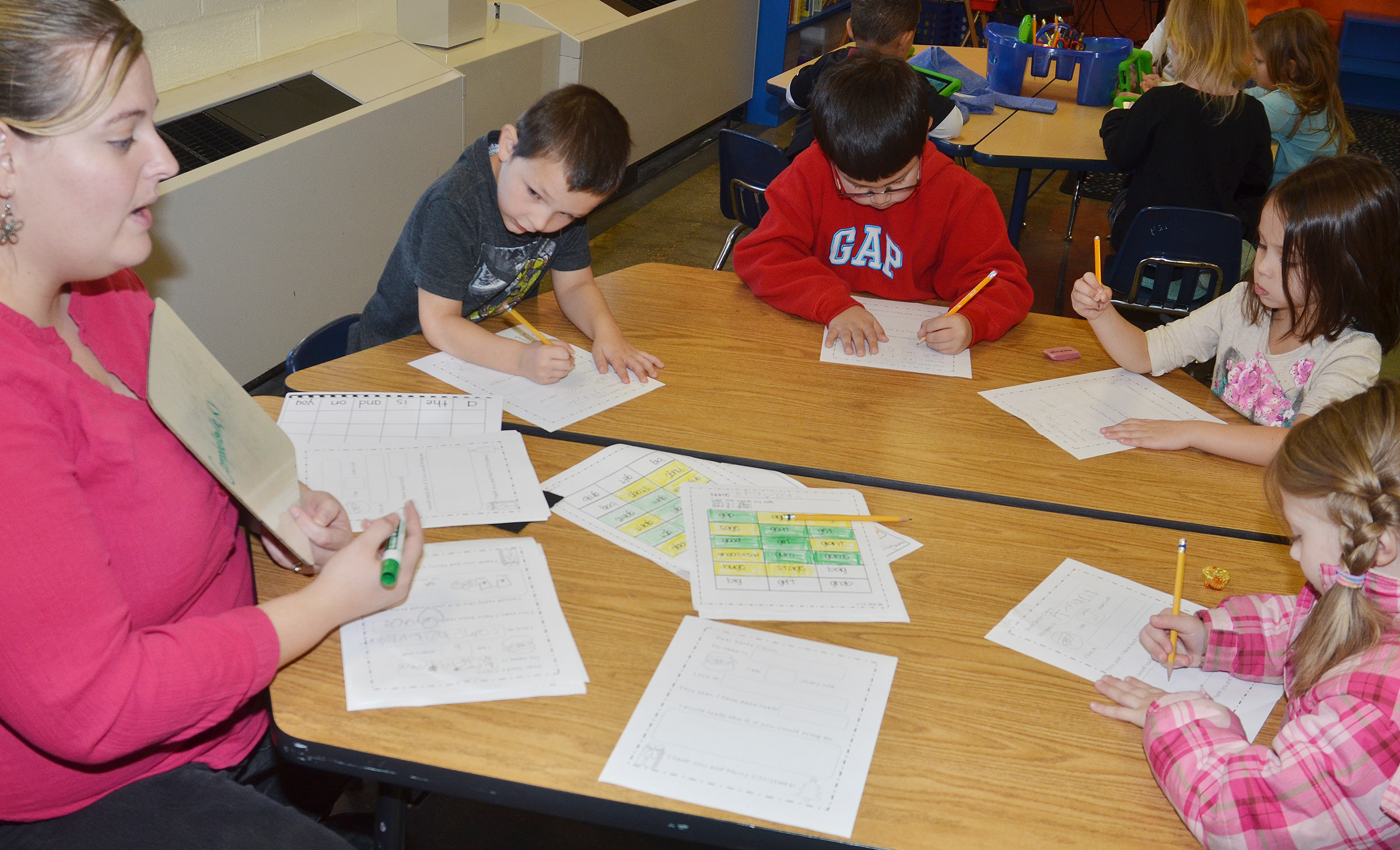 "CES kindergarten teacher Kimberly Clark helps her students, from left, Brayden Perkins, Victrin Ramsey, Tylee Britton and Amary Tompkins write the word ""Campbellsville"" in their letters to Santa."