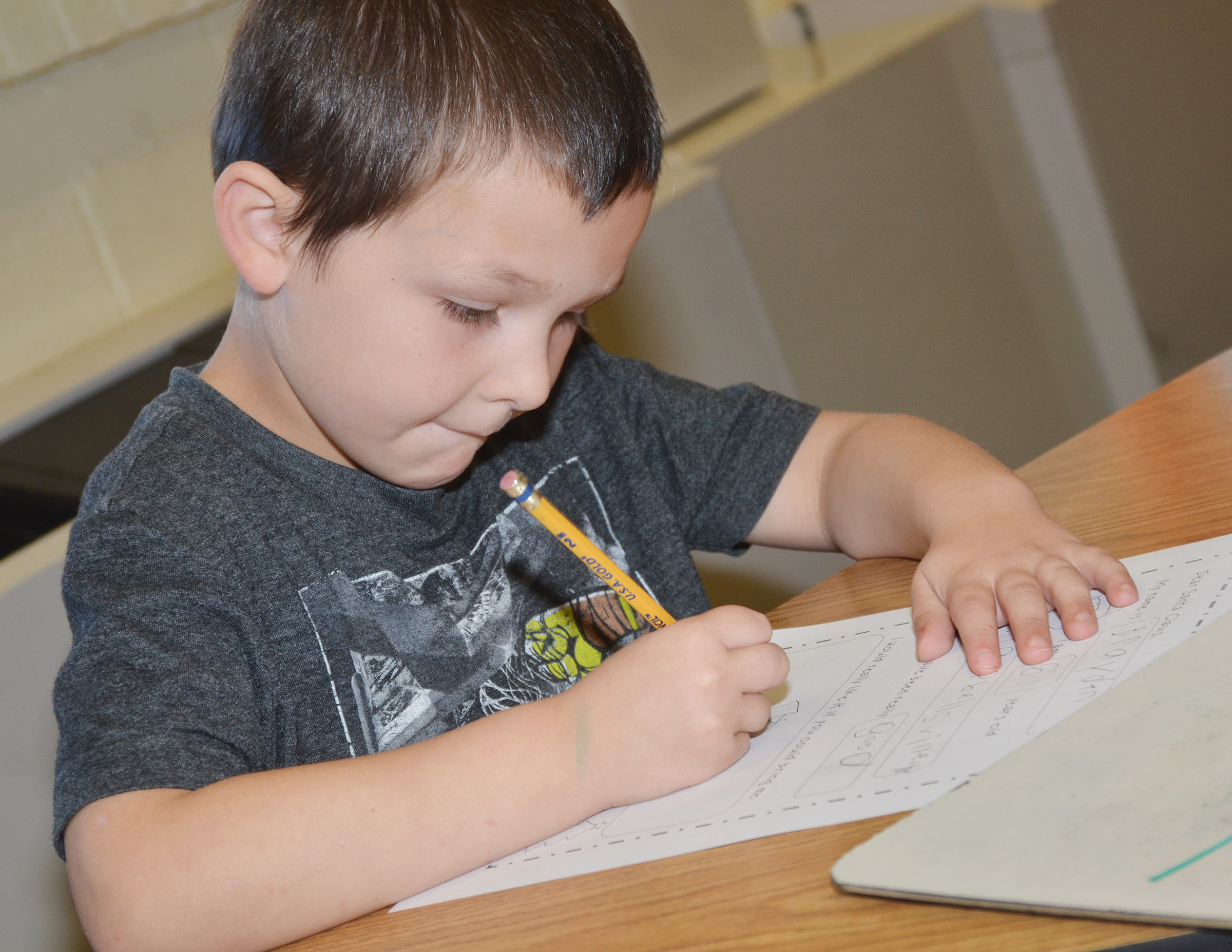 CES kindergartener Brayden Perkins writes his letter to Santa.