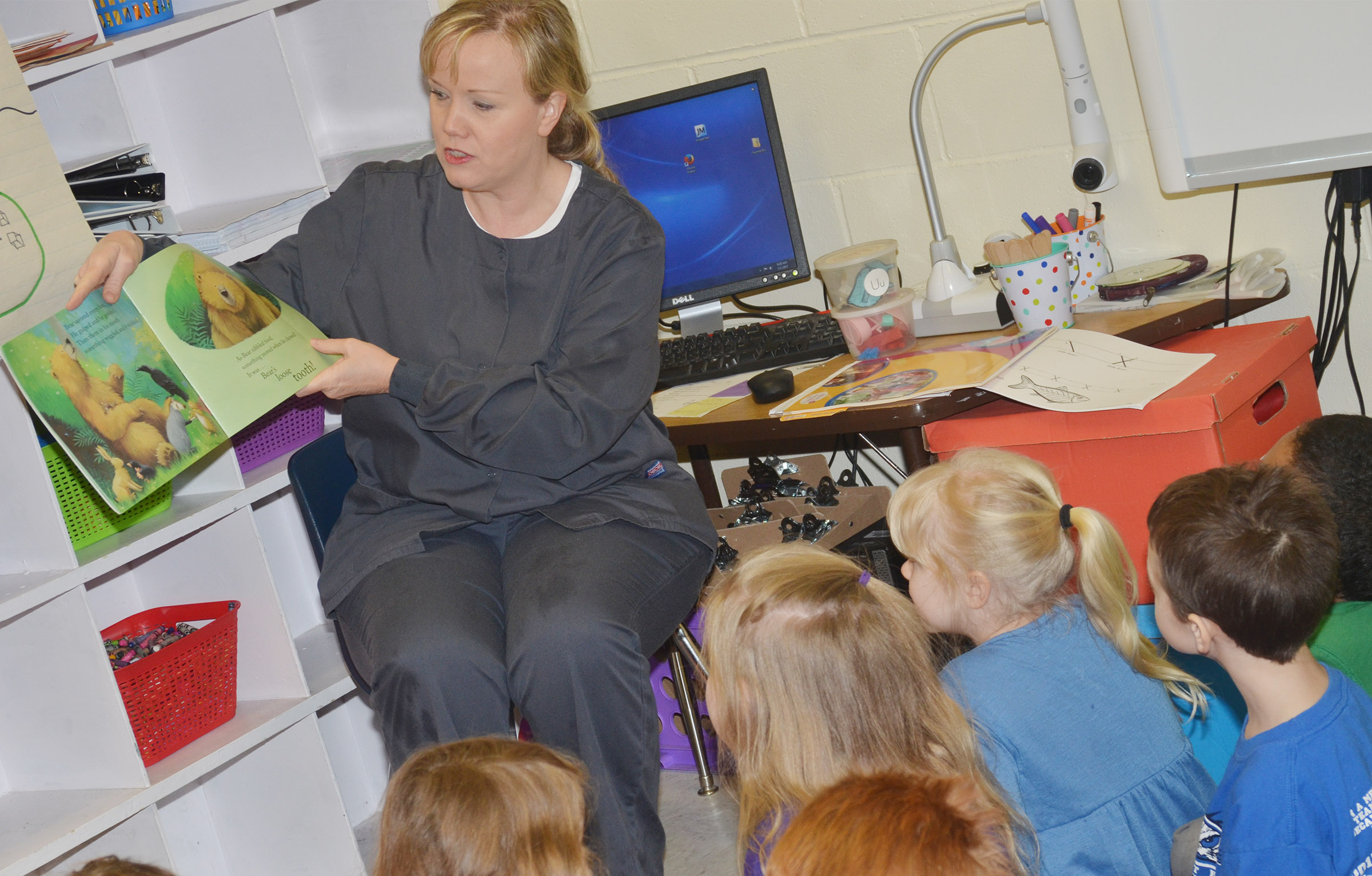 "Dental hygienist Jennifer White, who works at Dr. Randy Smoot's dental office in Campbellsville, reads ""Bear's Loose Tooth"" to CES kindergarteners."