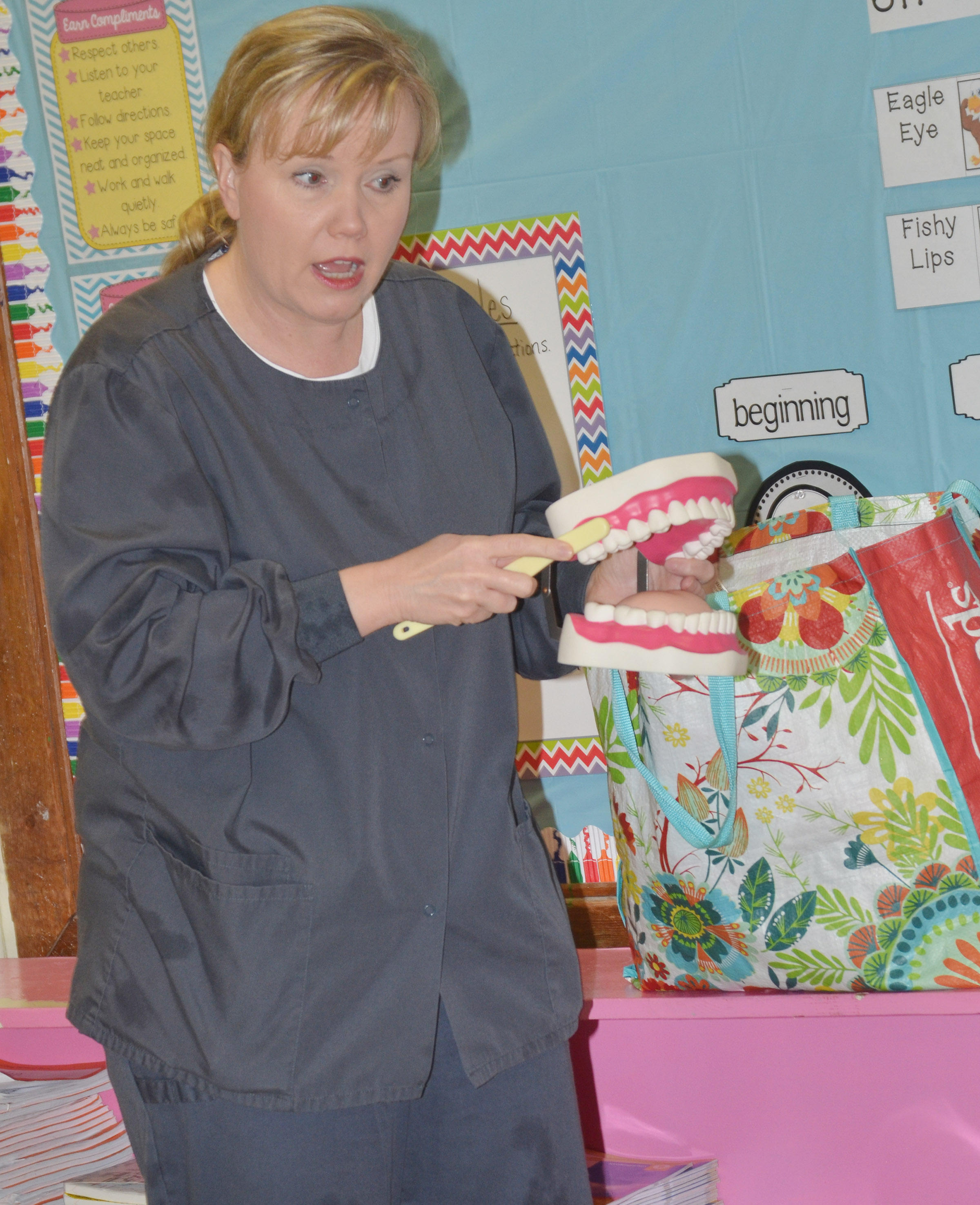 Dental hygienist Jennifer White, who works at Dr. Randy Smoot's dental office in Campbellsville, tells CES kindergarteners the proper way to brush their teeth.