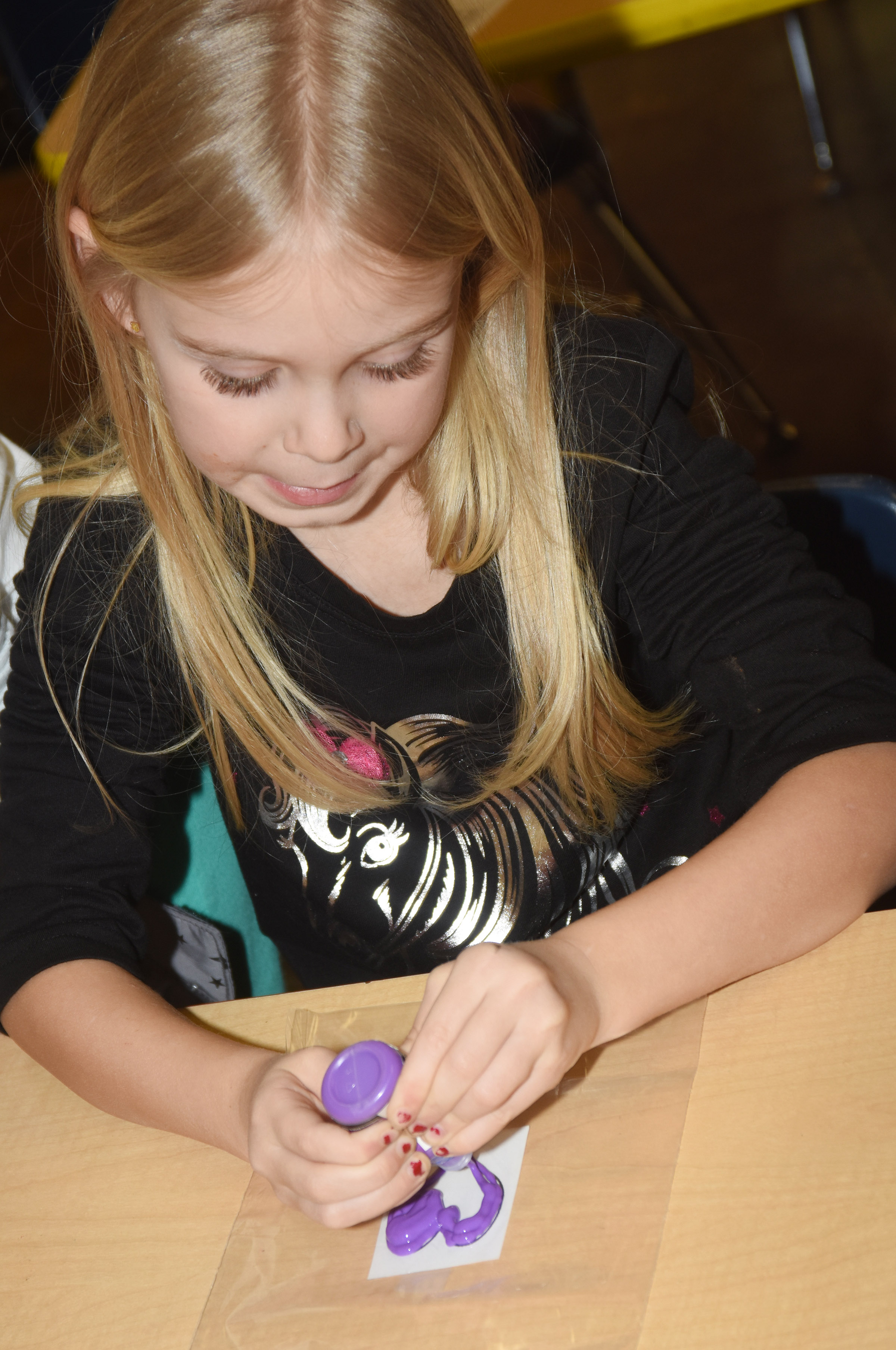 CES kindergartener Alinna Bray paints a heart as she makes her window cling.