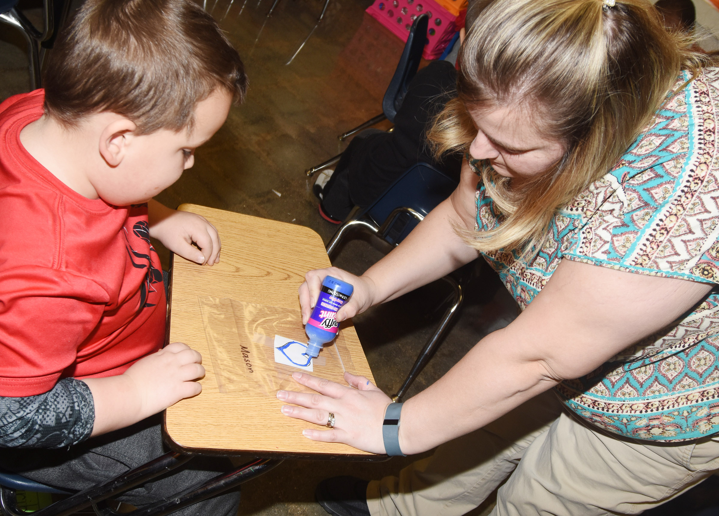 CES kindergarten teacher Kimberly Clark helps Mason Gribbin paint a heart for his window cling.