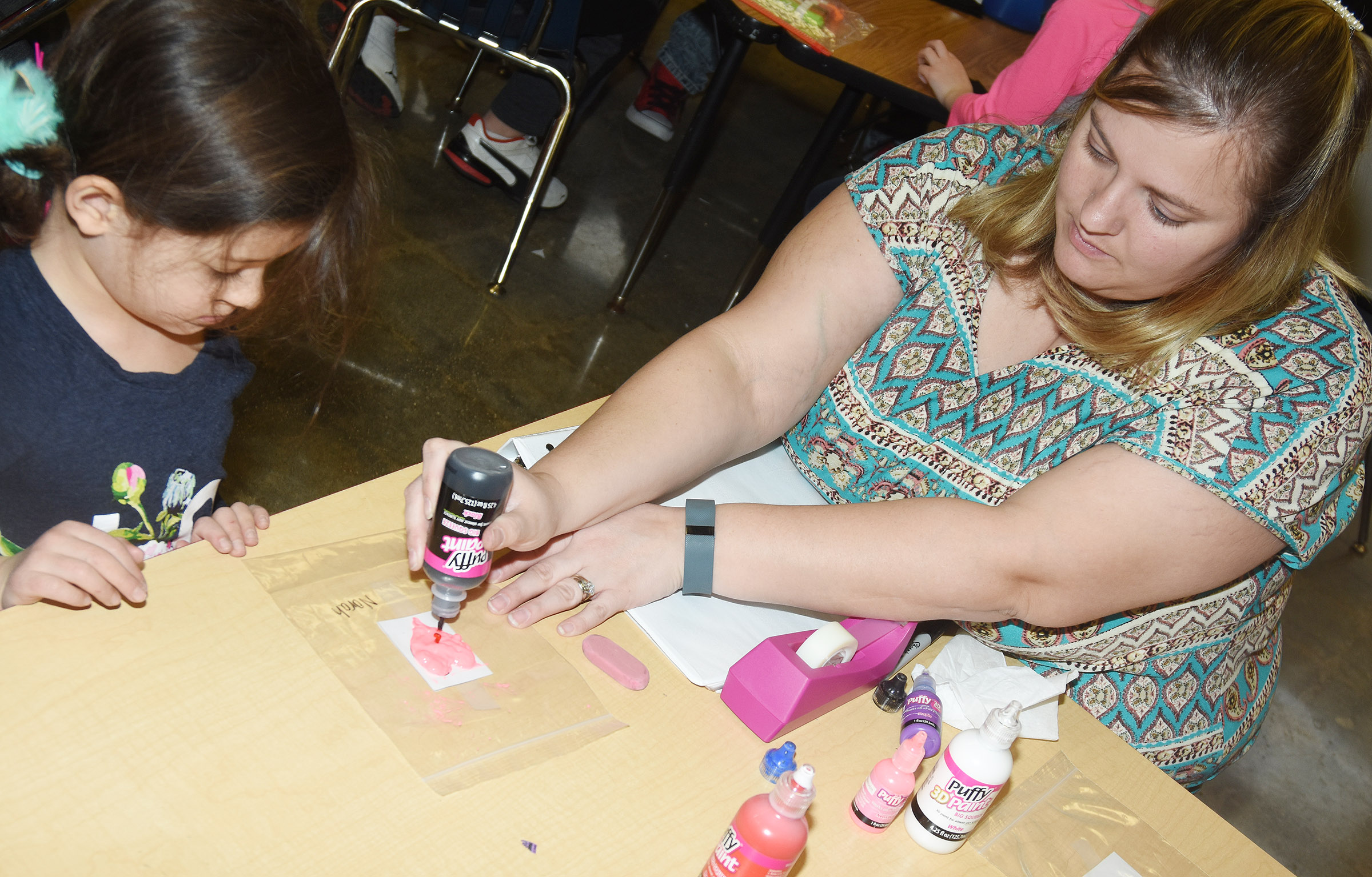 CES kindergarten teacher Kimberly Clark helps Norah Adkins paint a heart for her window cling.