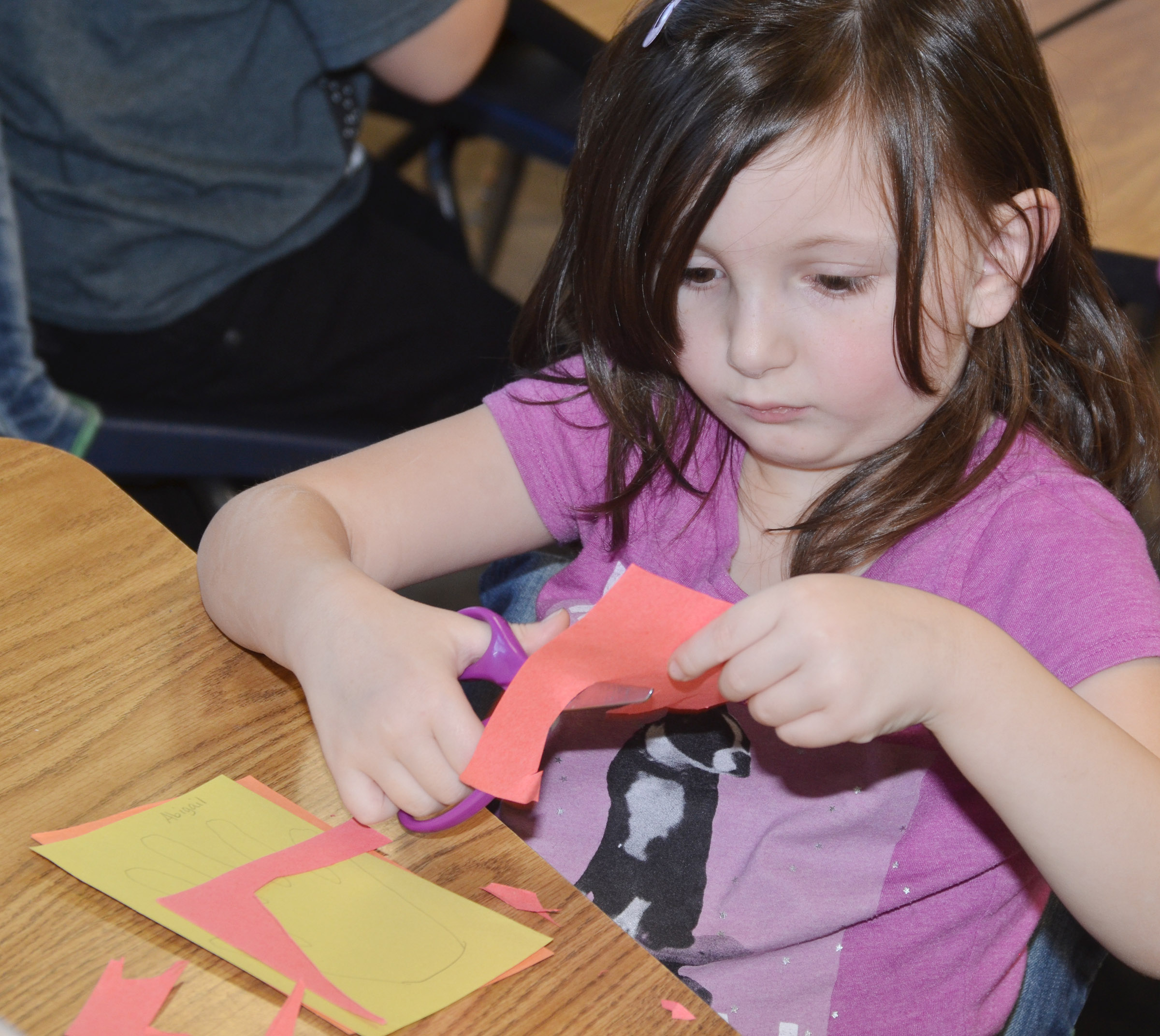 CES kindergartener Abigail Smith cuts out her hands as she makes a turkey.