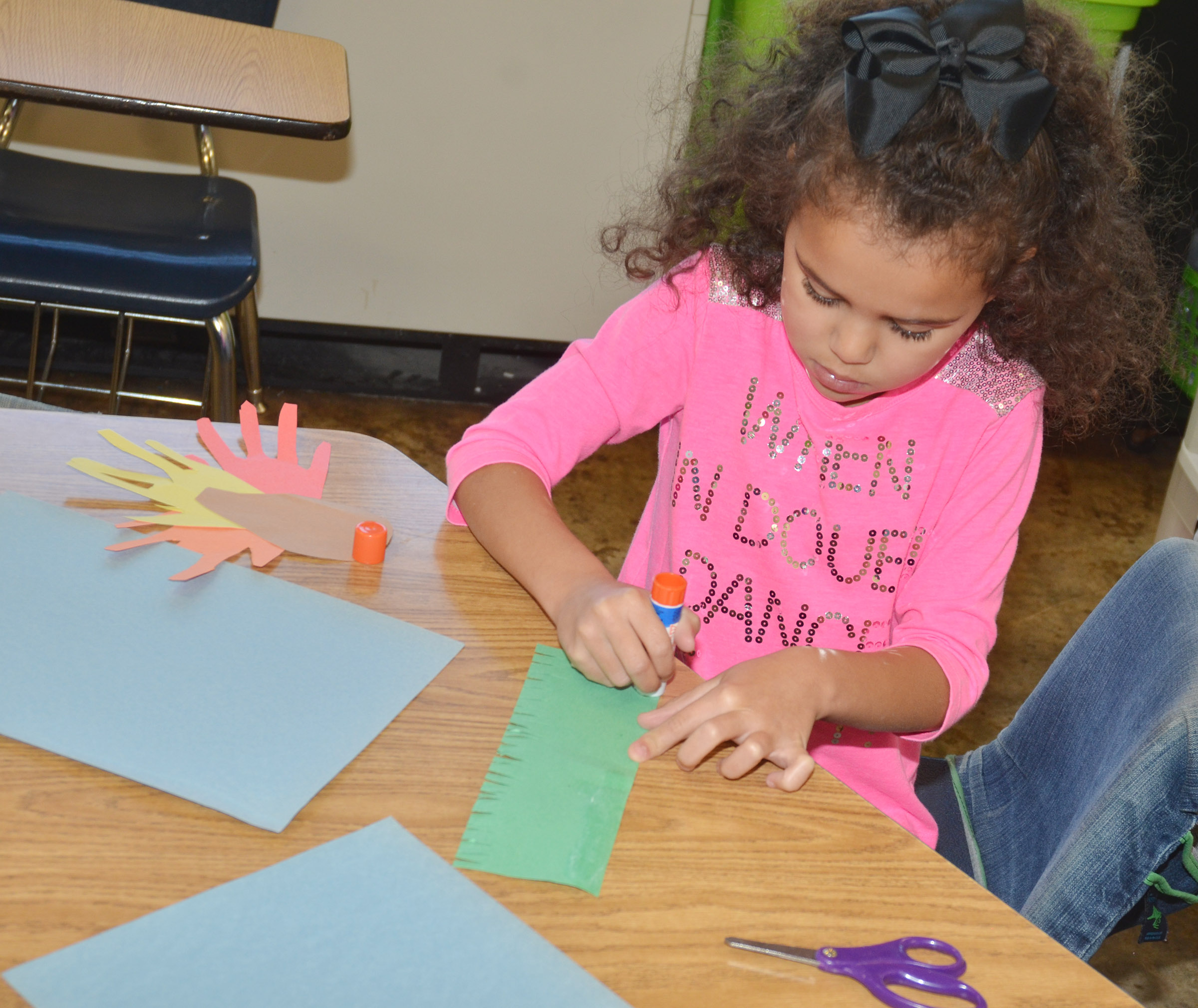 CES kindergartener Addie Litsey glues grass on her construction paper as she makes her turkey.