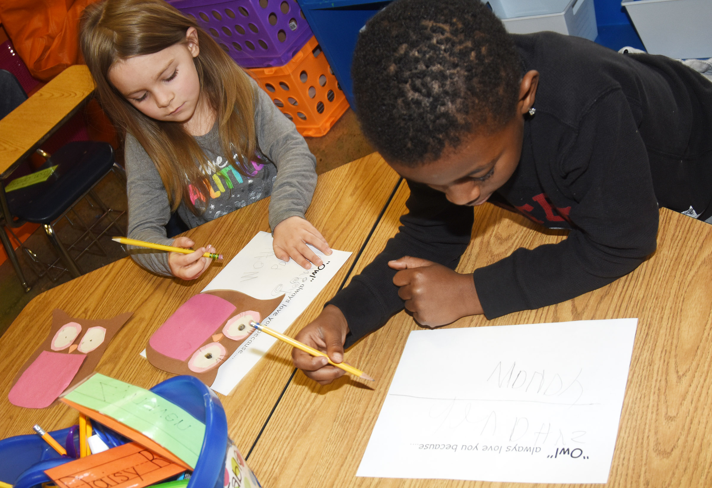 CES kindergarteners Daisy Rakes, at left, and Zyhaven Taylor finish their Valentine writing.