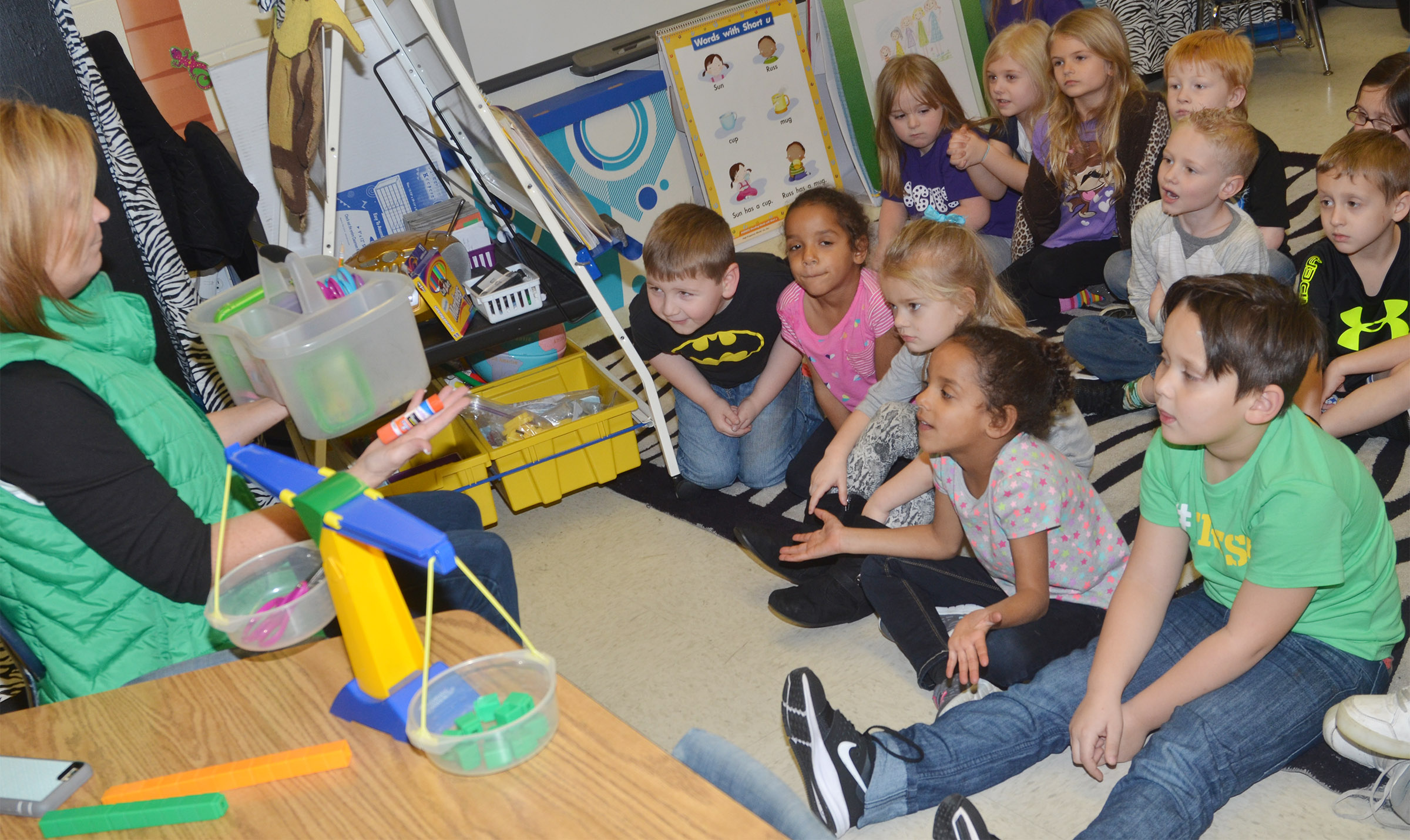CES kindergarten teacher Lisa Wiseman helps students learn that the weight of an object can't always be determined by how big it is.