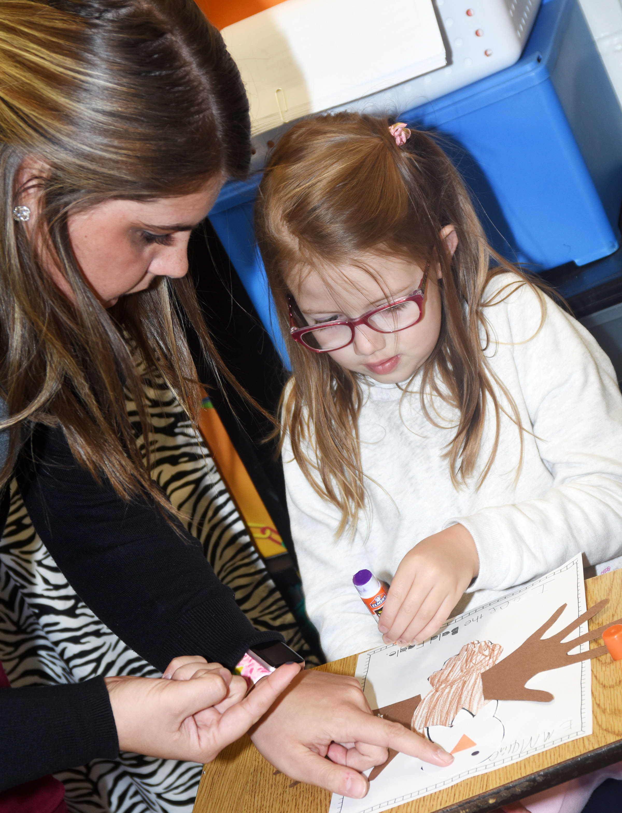 CES kindergartener Emmaline Vespie adds eyes to her bald eagle, with some help from student teacher Shelby Carney.