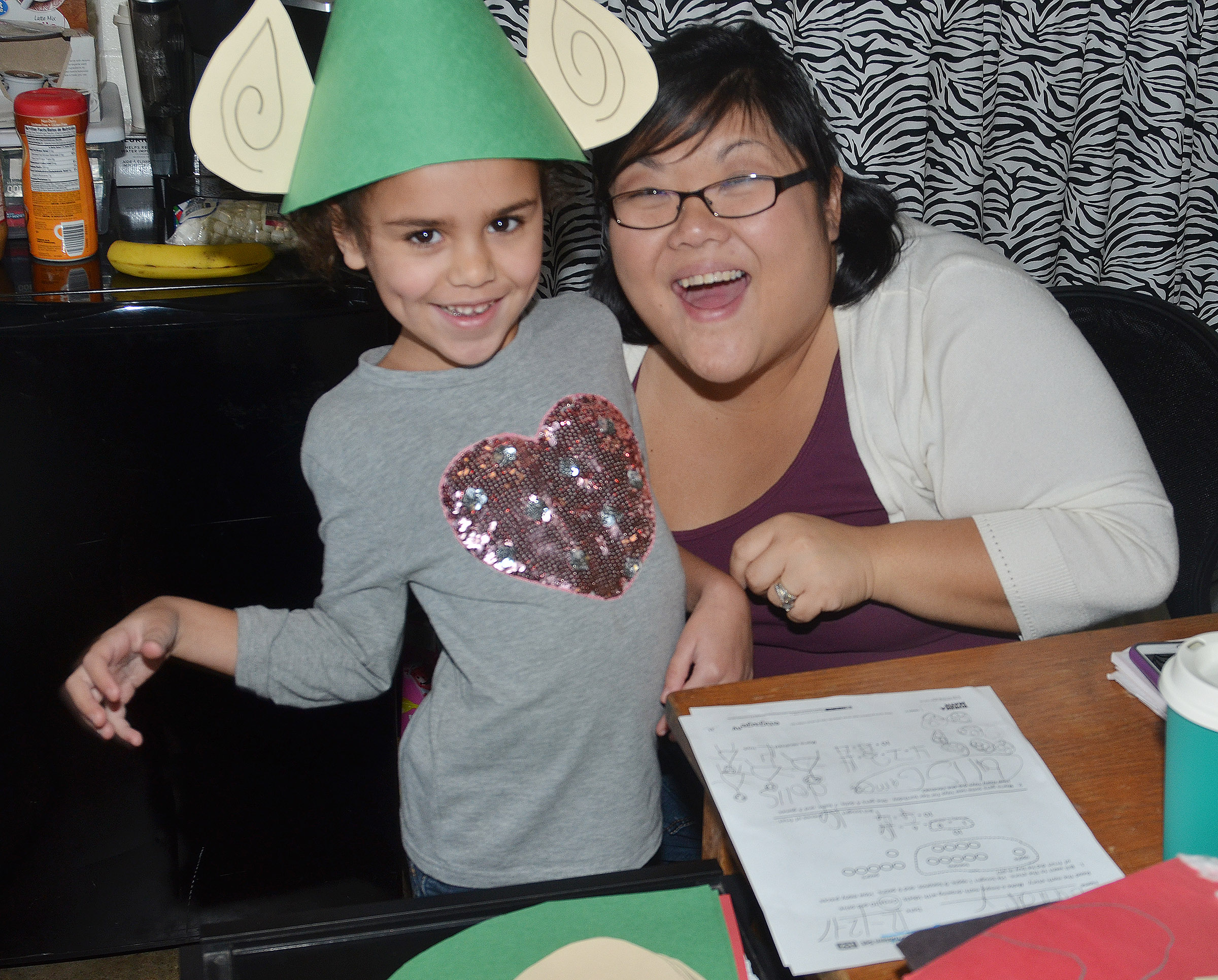 CES kindergarten assistant Brittany Johnson poses with Adelyn Litsey as she wears her elf hat.