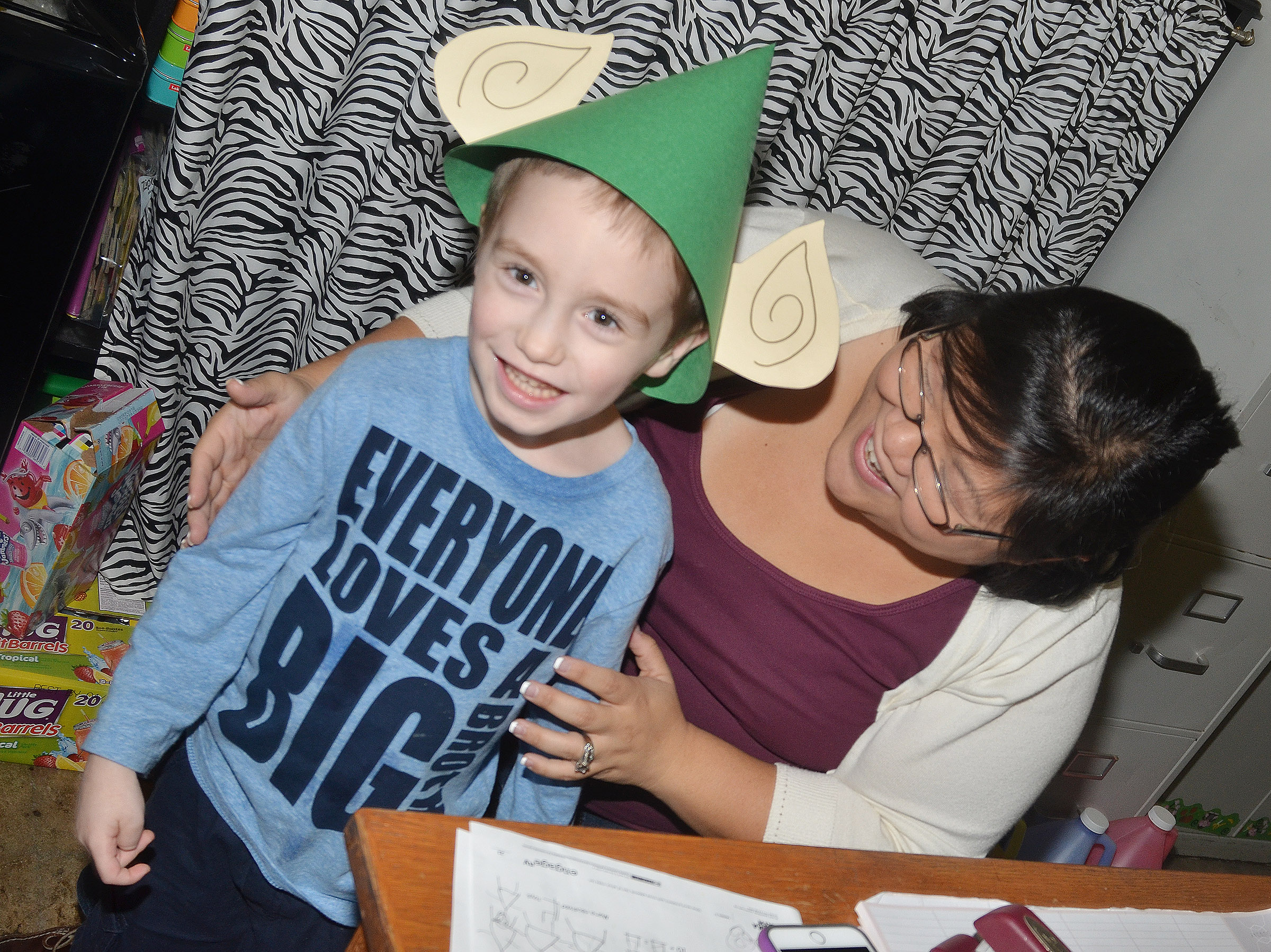 CES kindergarten assistant Brittany Johnson helps Joshua Dickens try on his elf hat.