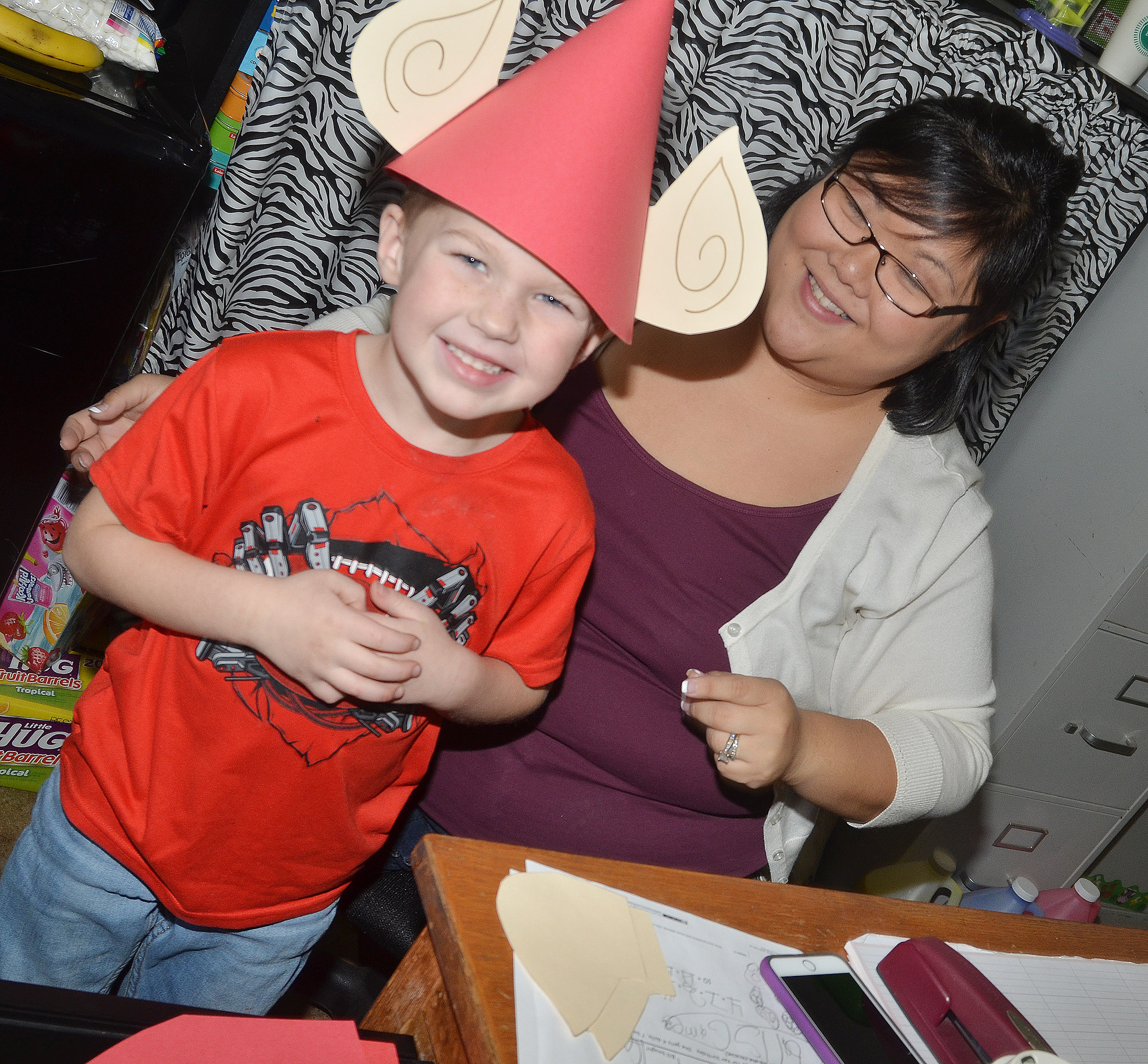 CES kindergarten assistant Brittany Johnson helps Landry Brown try on his elf hat.