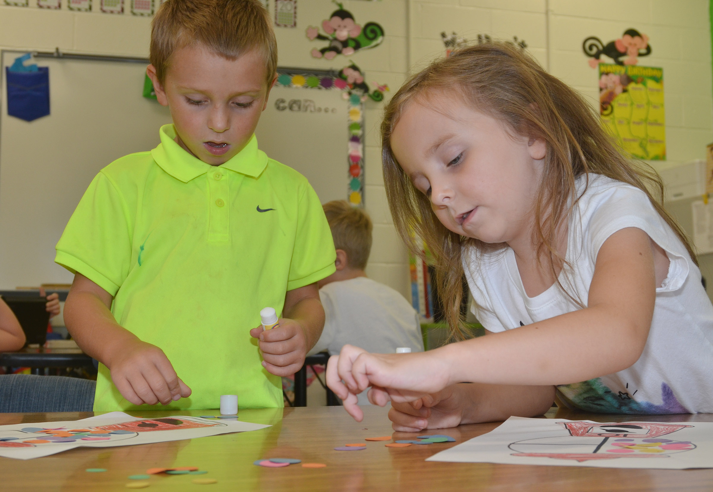 CES kindergarteners Brayden Taylor, at left, and Tabitha Leggett count 10 gumballs to add to their gumball machines.