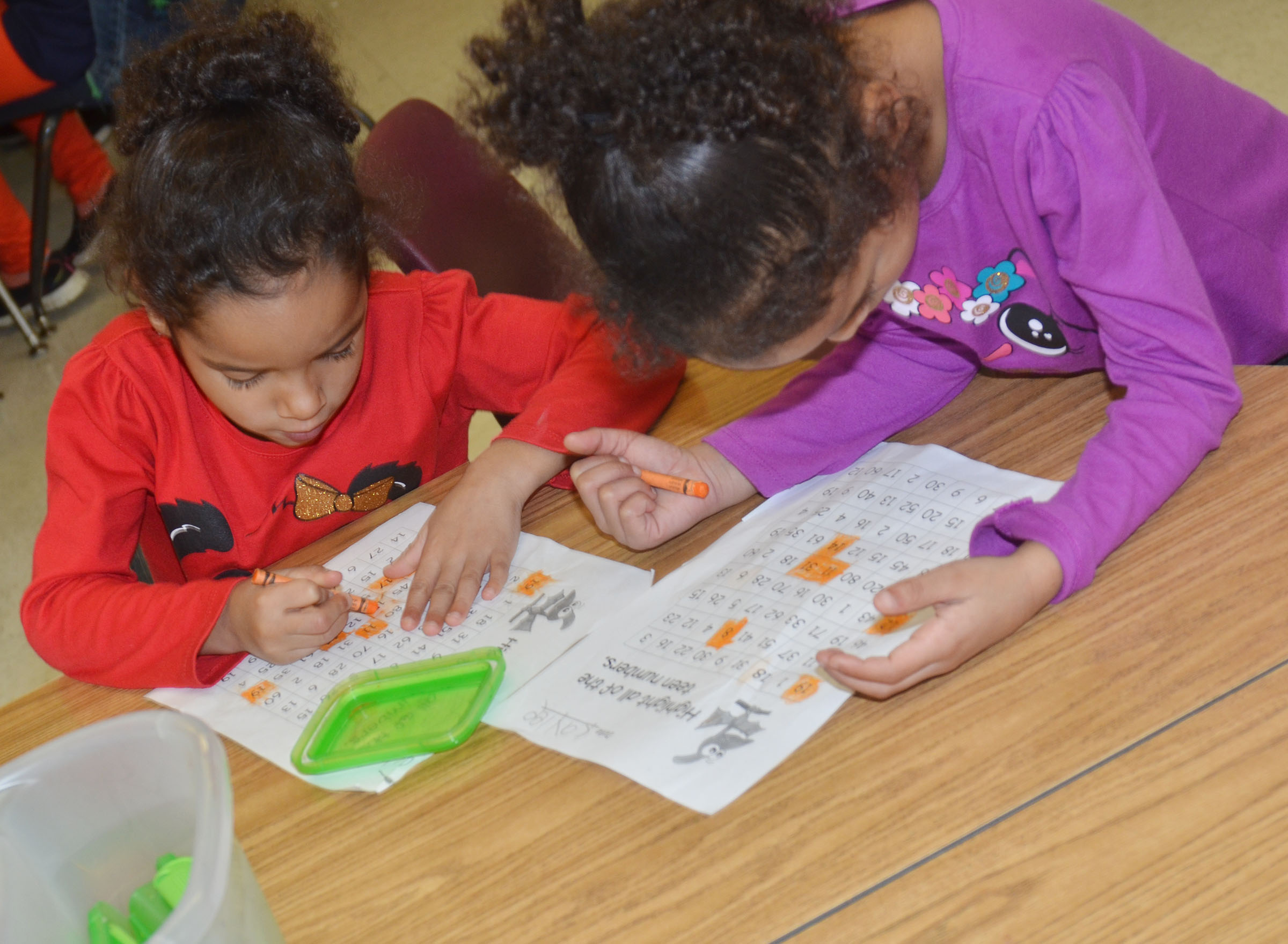 "CES kindergarteners Kylei Thompson, at left, and her twin sister Kaylee Thompson color the ""teen"" numbers on their worksheet."