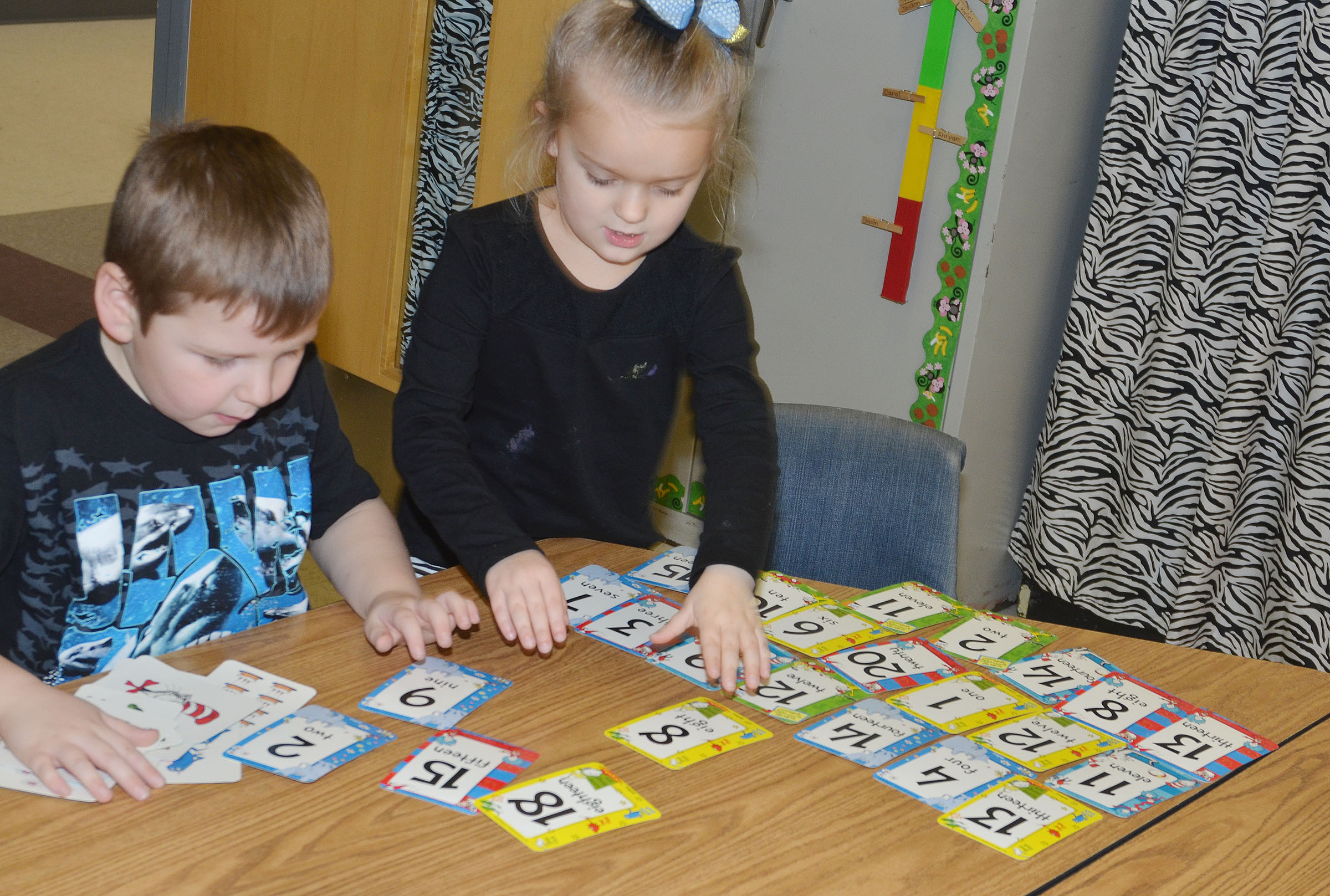 CES kindergarteners Enrique McDonald and Miley Orberson play a math card game.