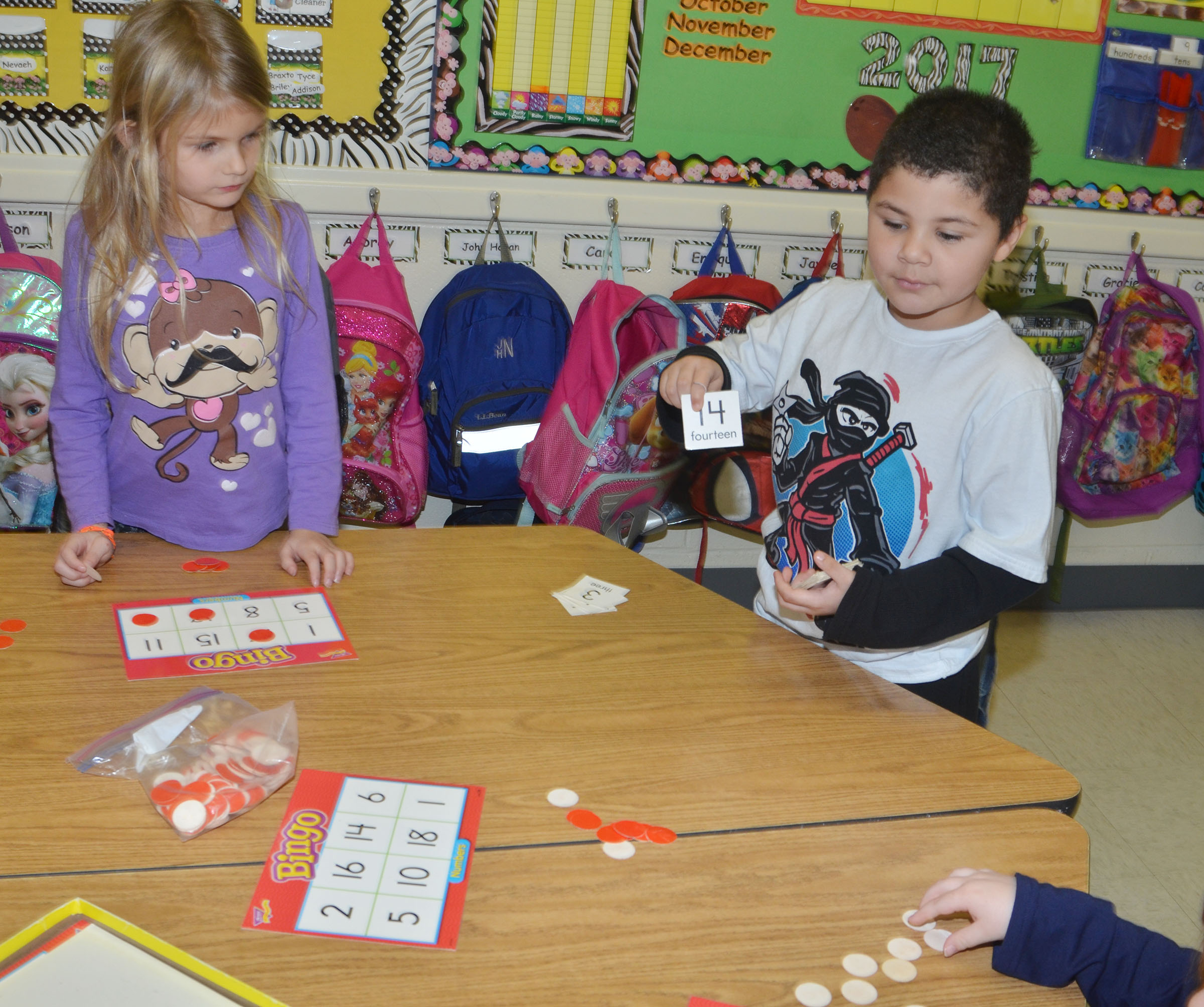 CES kindergarteners Gracie Gebler, at left, listens as classmate NyJah Vaught calls a number while her group plays math Bingo.