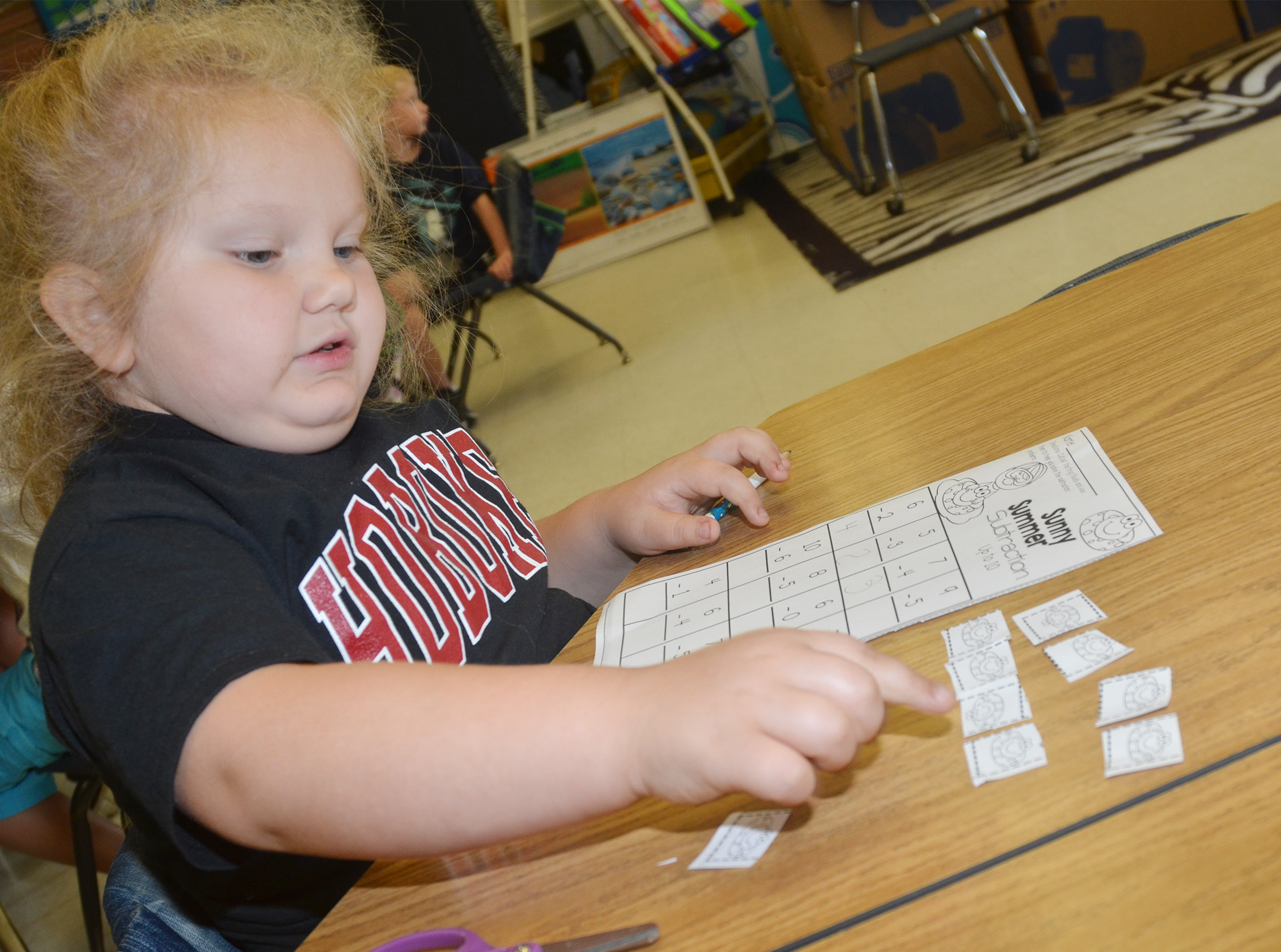 CES kindergartener ReAnna Jeffries uses pictures to help her work a subtraction problem.