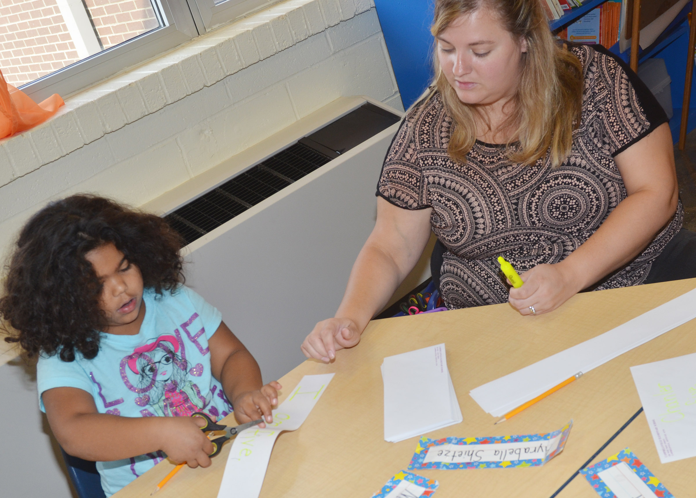 CES kindergartener Kimberly Clark helps student Linnly Adams cut out the words of her sentence.