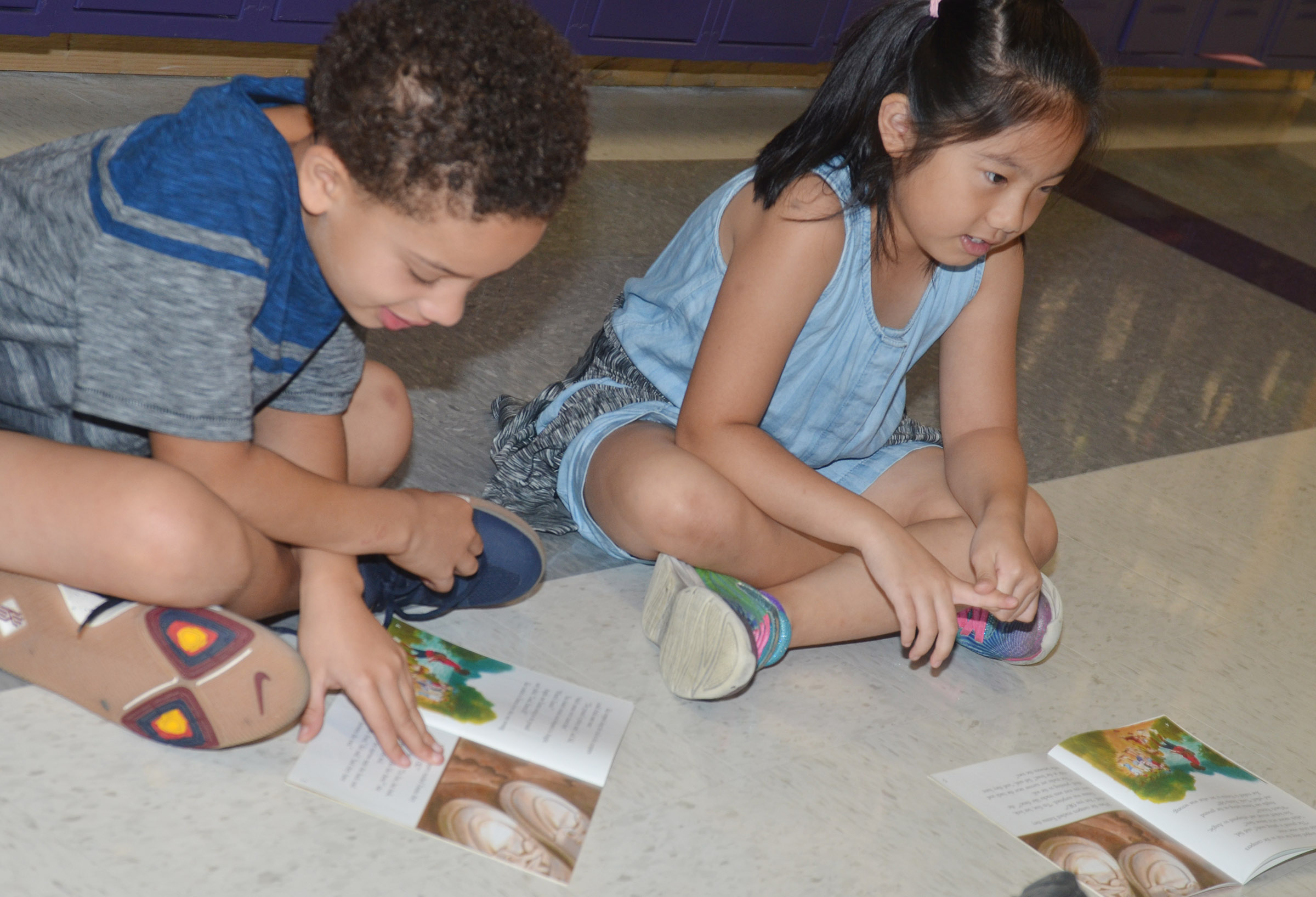 "CES second-graders Bryant Mayo, at left, and Tina Jiang read ""The Mysterious Animal Tracks."""
