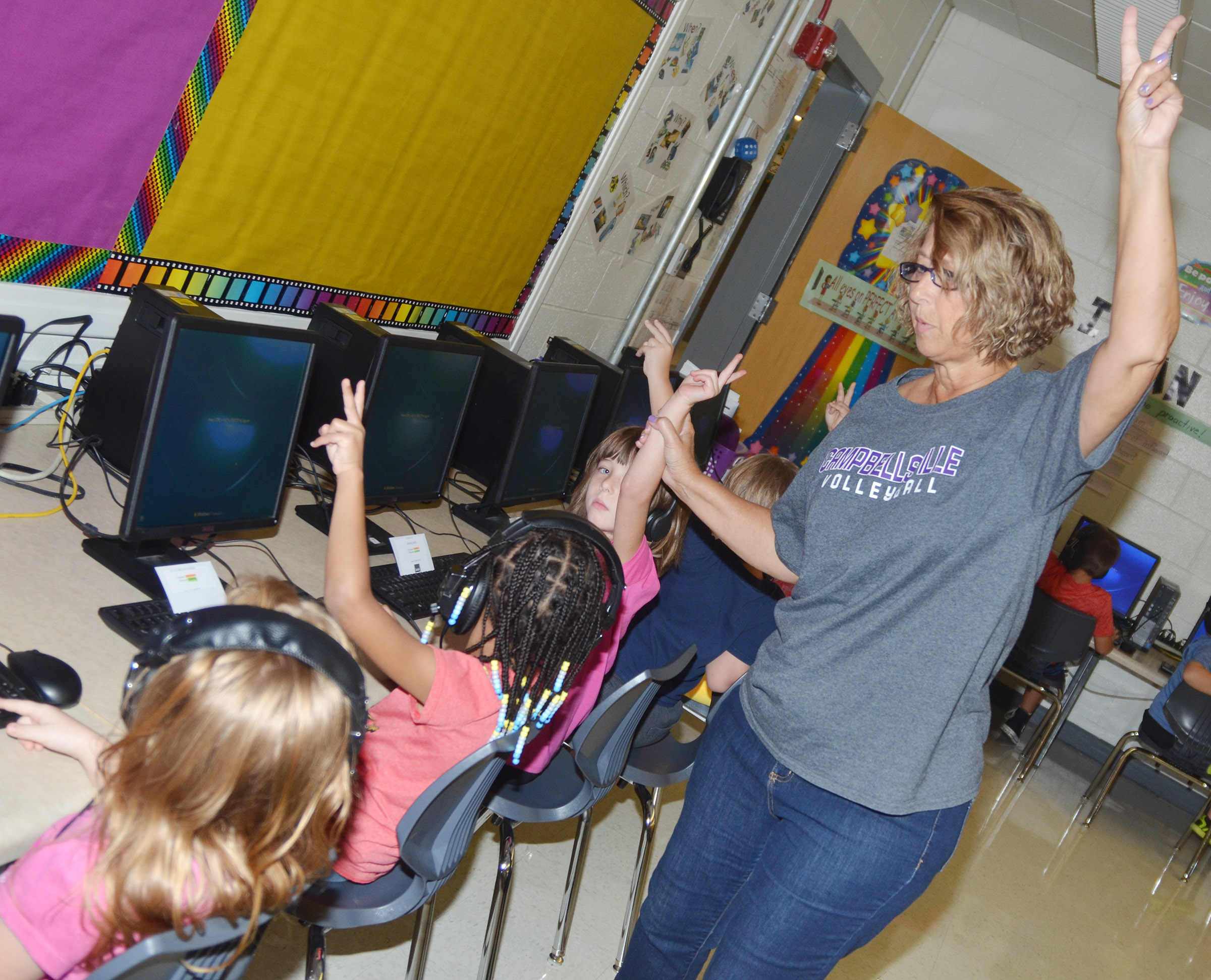 CES teacher Beverly Knifley teaches her first-grade students a trick to logging on their computer.