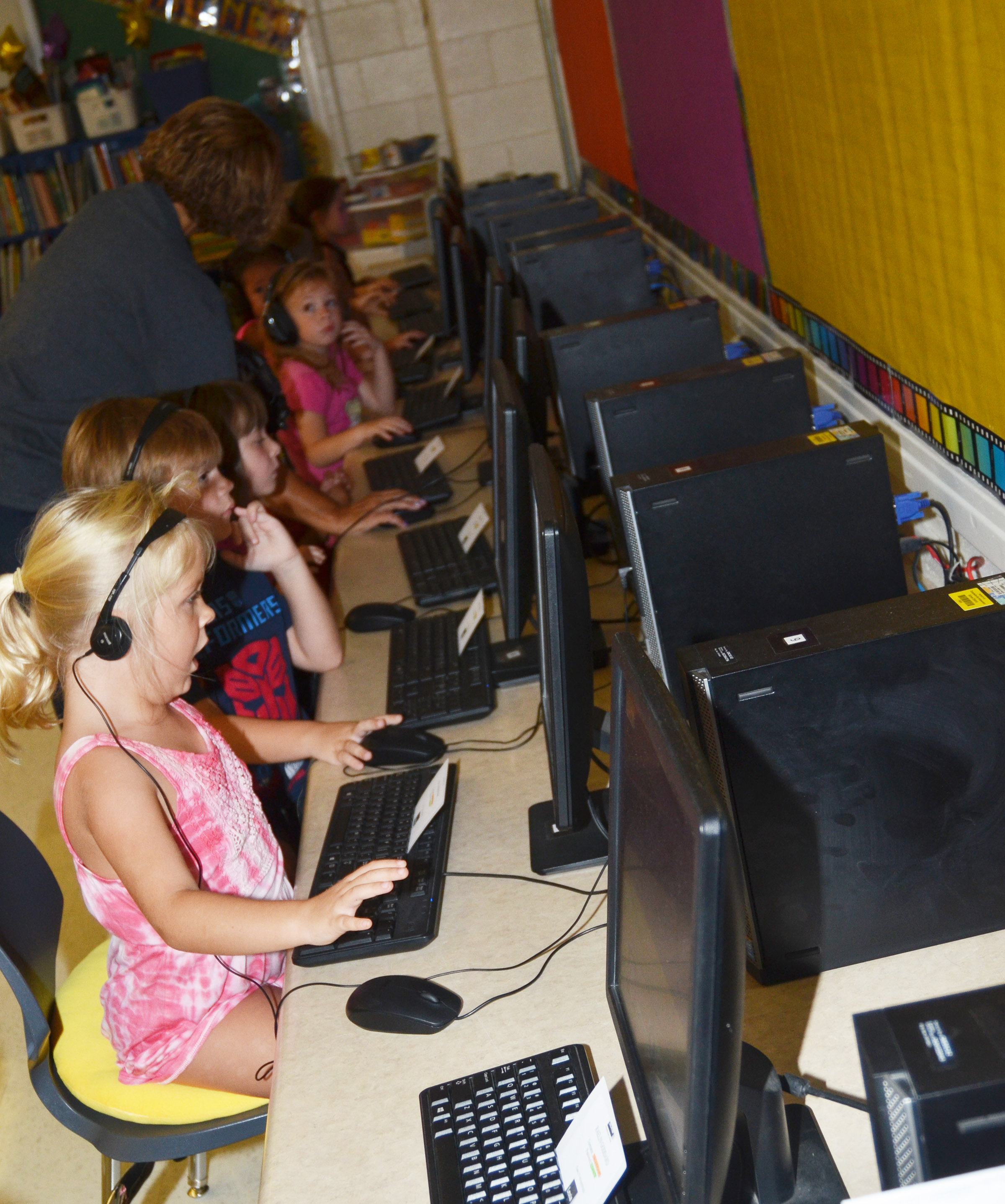 CES teacher Beverly Knifley helps first-graders enter their usernames and passwords.