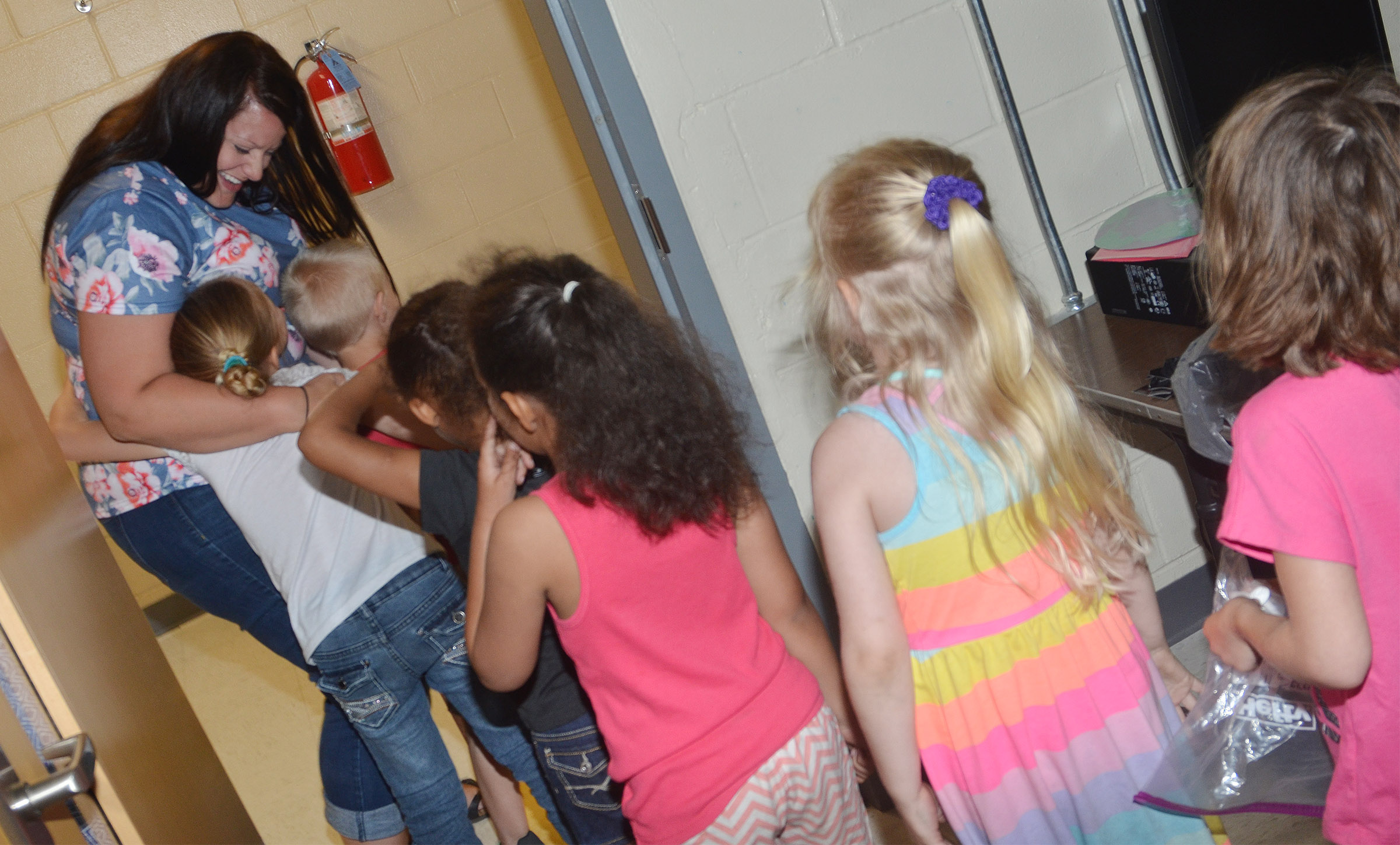 CES kindergarteners hug CES Explorers teacher Miriah Cox on the last day of school.