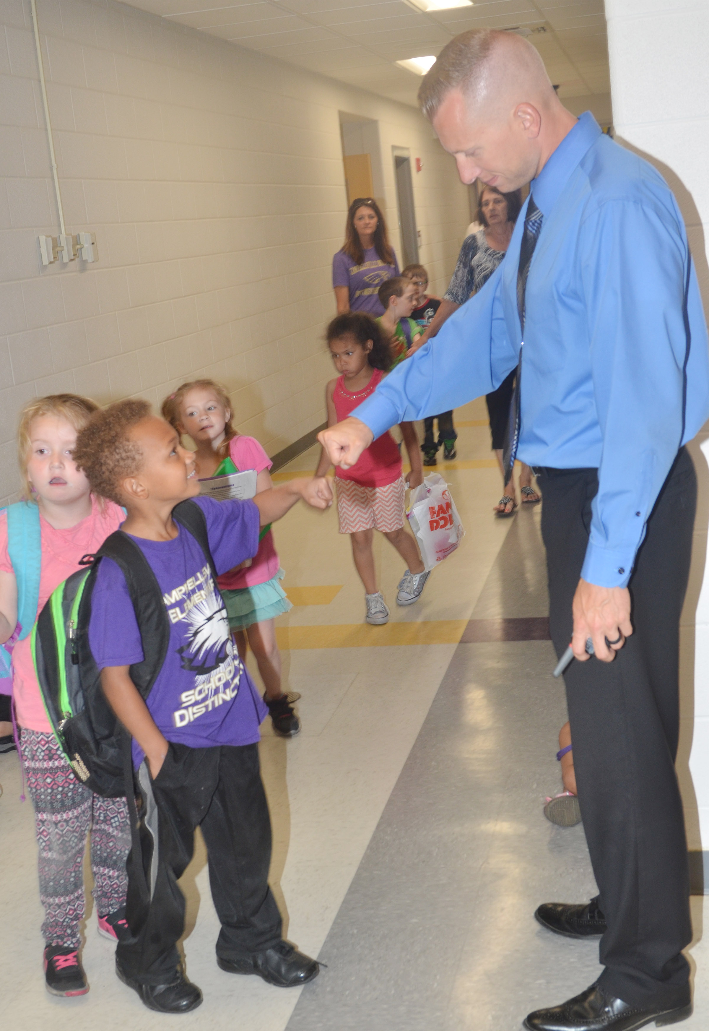 CES Assistant Principal Zach Lewis bumps fists with kindergartener Treshaun Robinson as he gets ready to go home.