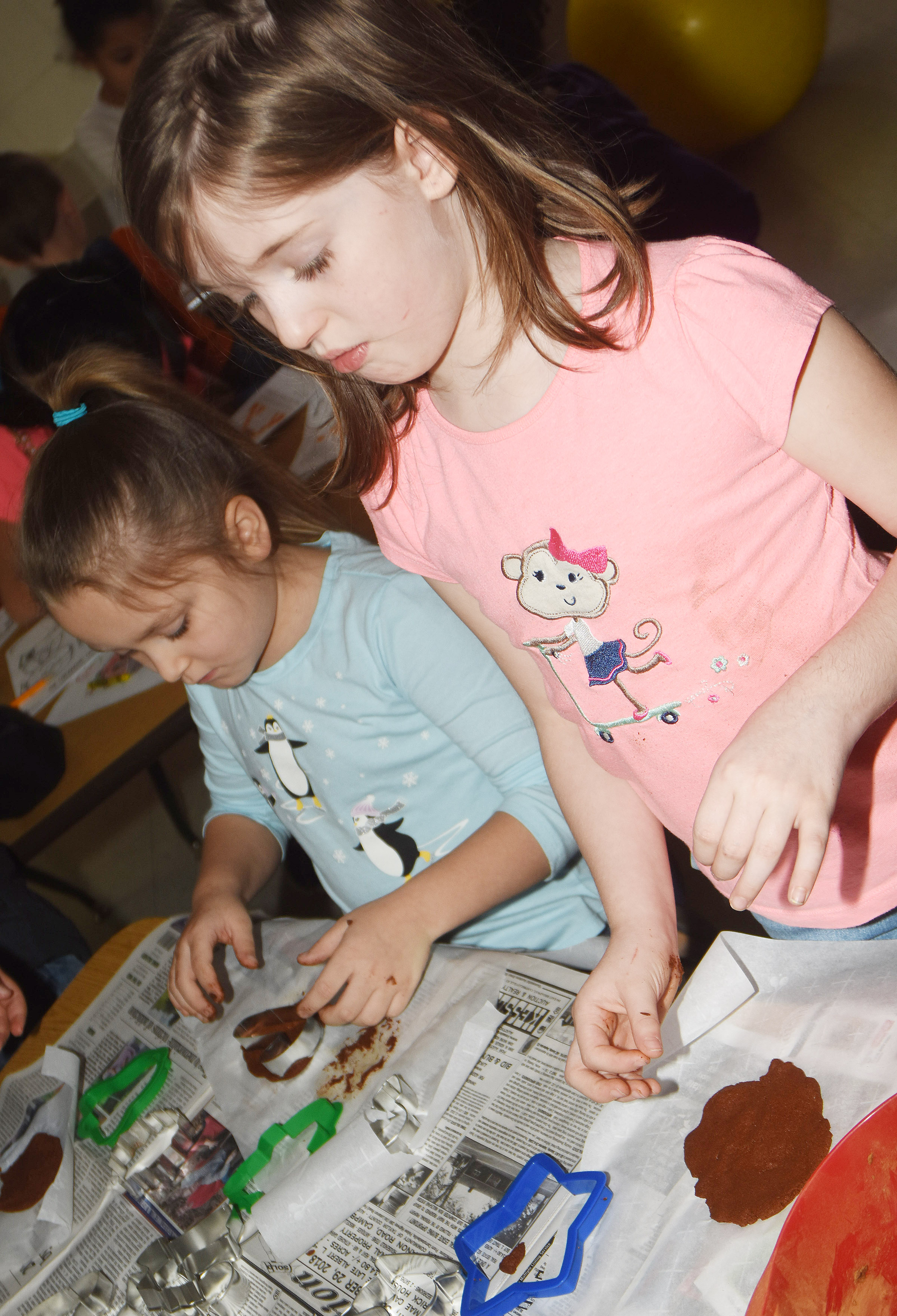 CES first-graders Myah Learmond, at left, and Lasca Martin flatten their dough to make their ornaments.