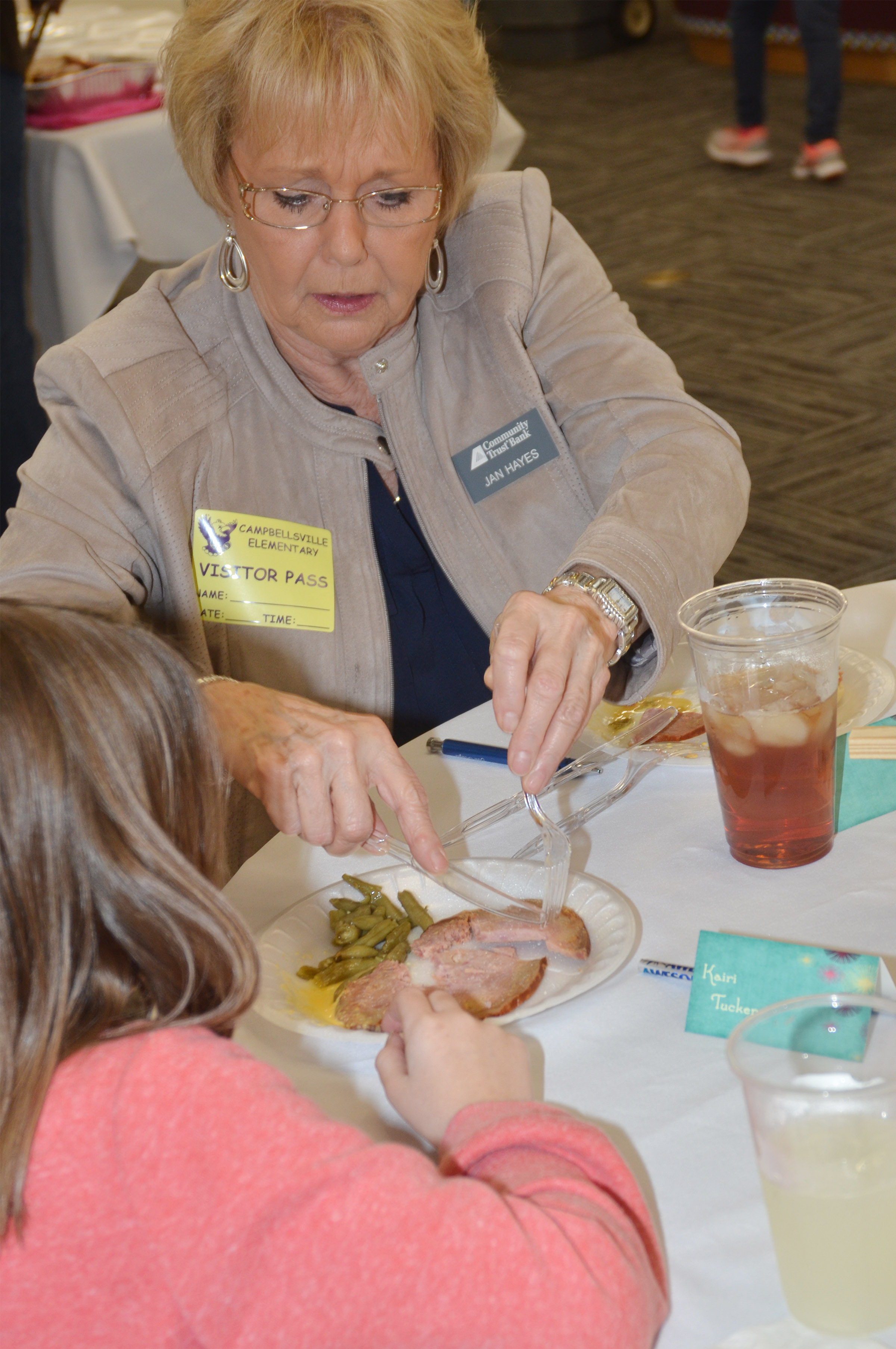 Jan Hayes, manager of Community Trust Bank, cuts second-grader Kairi Tucker's meat.