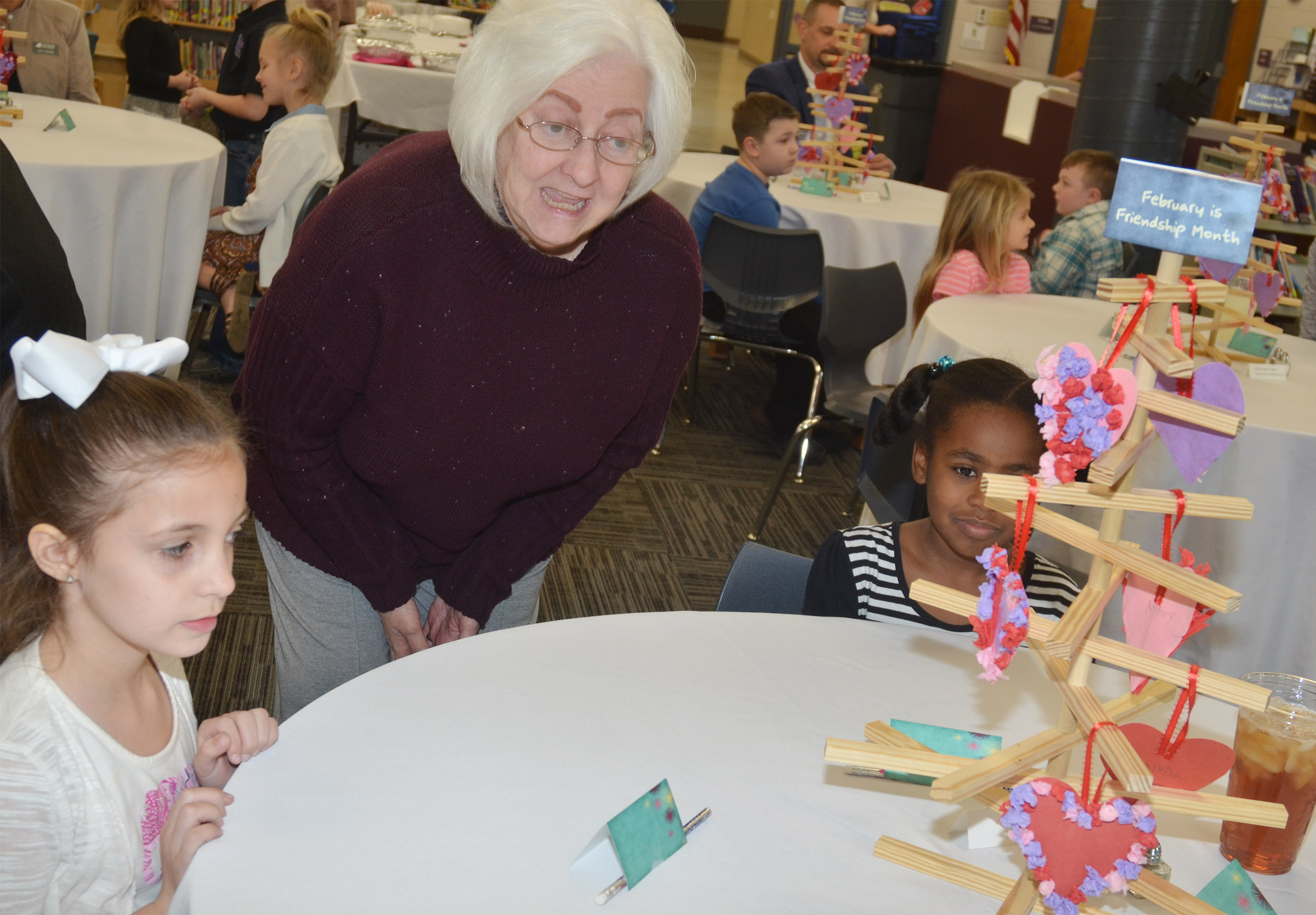 Campbellsville Board of Education Chair Pat Hall talks with first-graders Lillian Martin, at left, and Destini Gholston.