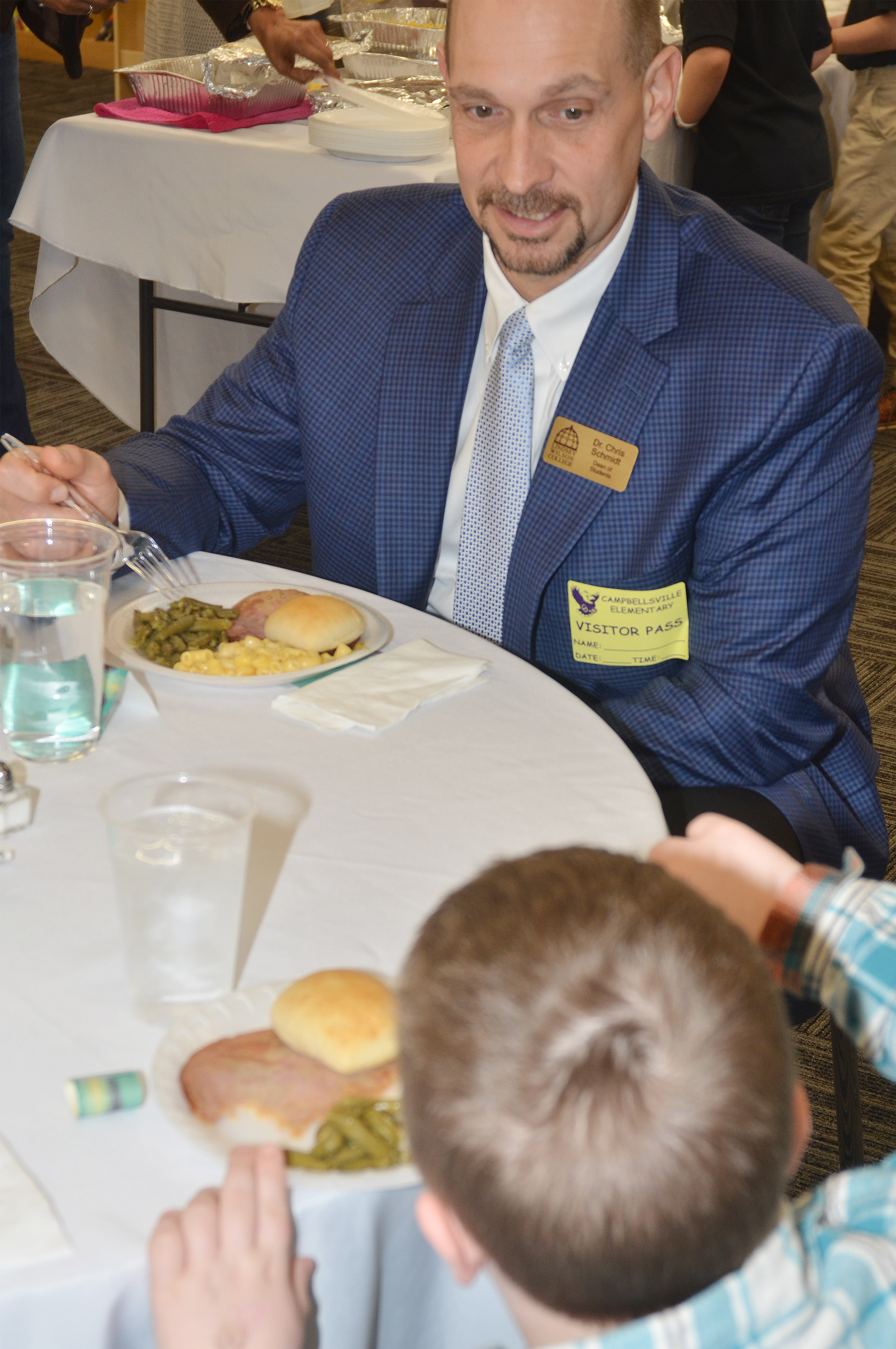 Dr. Chris Schmidt, dean of students at Lindsey Wilson College, has lunch with first-grader Hunter Clark.