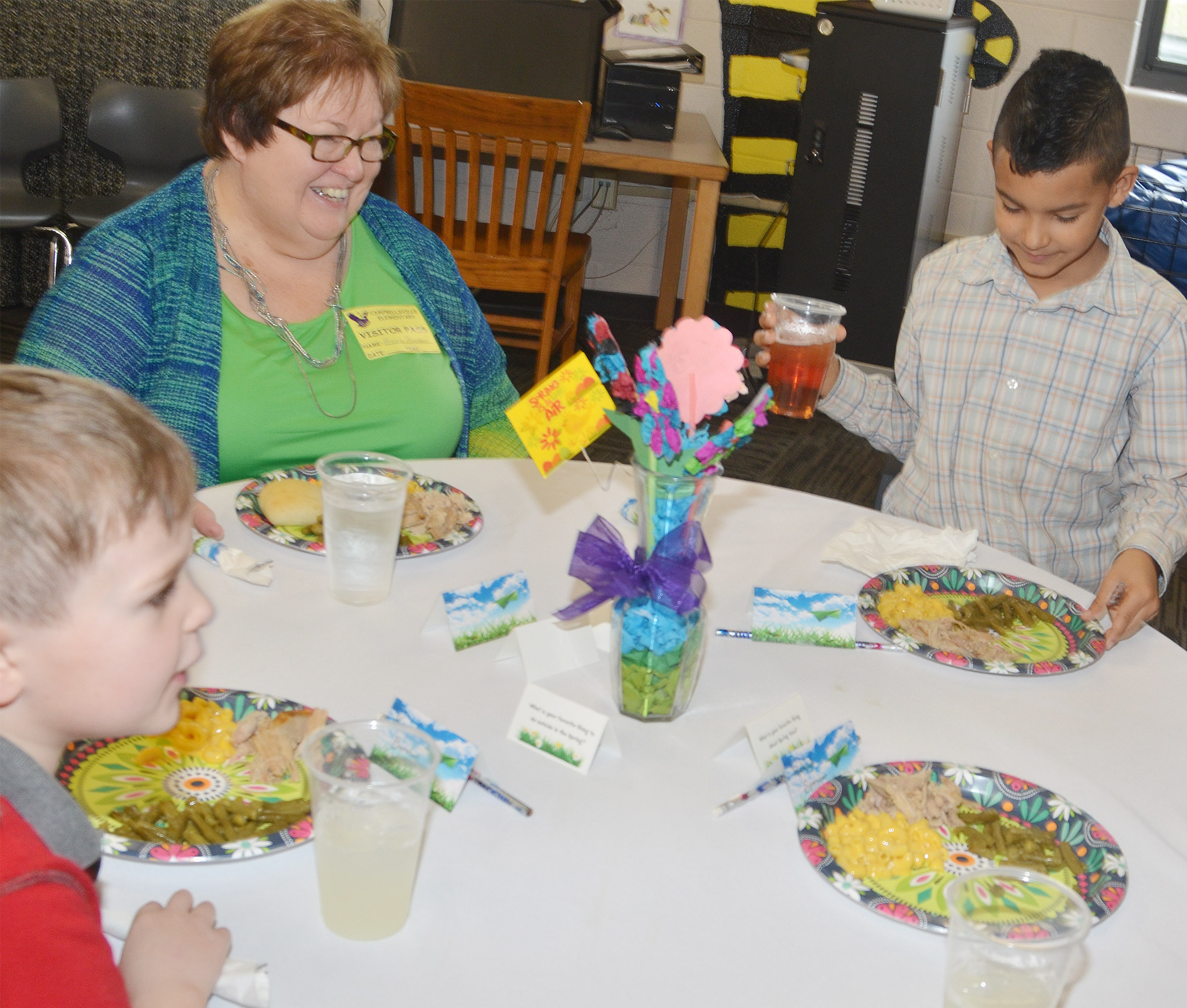 Beverly Rowland, dean and assistant professor in the School of Nursing at Campbellsville University, has lunch with first-graders Karson Burchett, at left, and Rizzo McKenzie.
