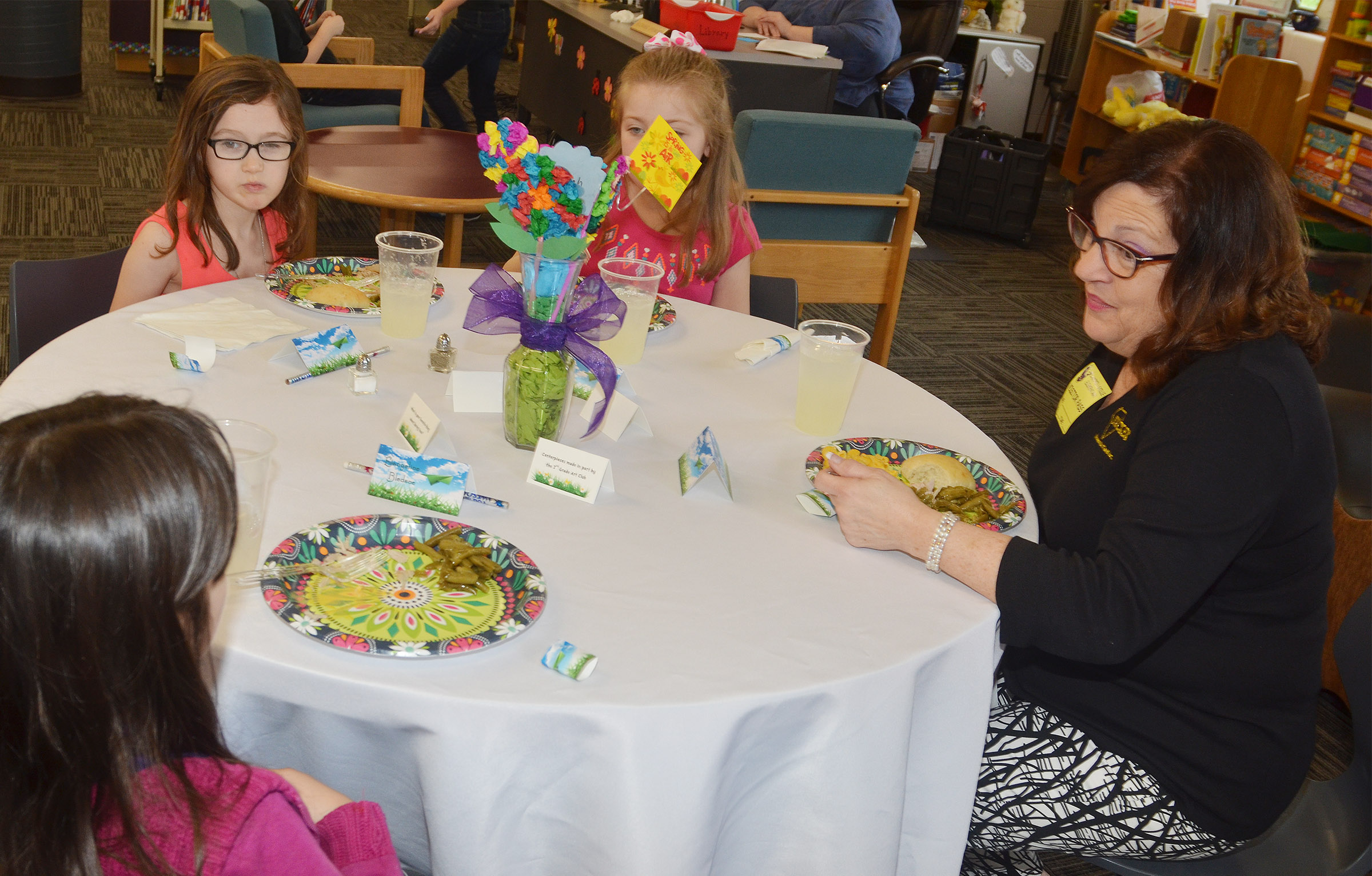 Kathleen Tucker, owner of Tucker Diamonds & Gold, talks with CES third-grader Evangeline Bledsoe.