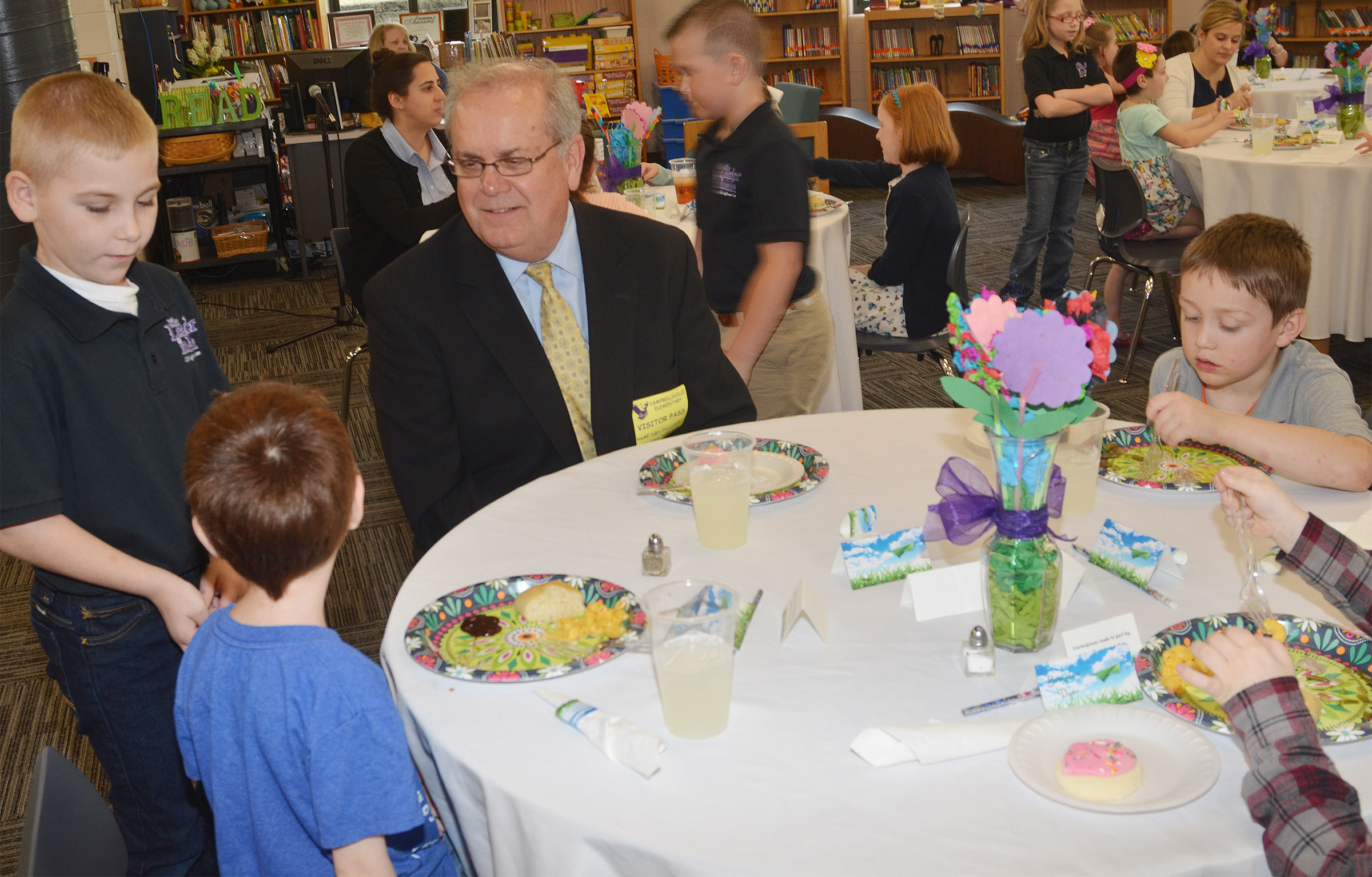 CES Lighthouse Team member Joseph Greer, a second-grader, asks kindergartener Carson Montes if he would like dessert.