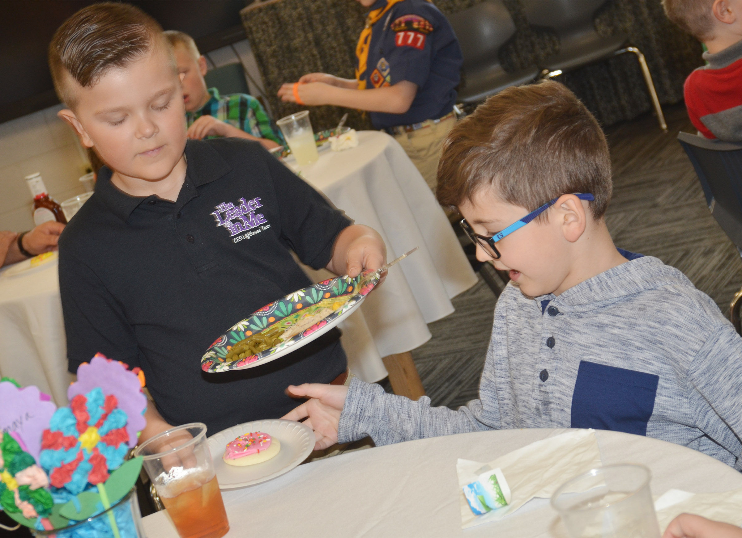 CES Lighthouse Team member Cayton Lawhorn, a second-grader, gives Tye Rhodes, also a second-grader, his dessert.