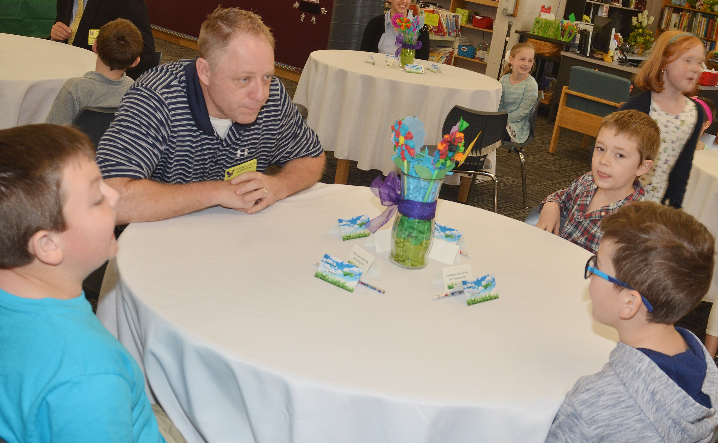 Brian Rafferty, lead pastor at Elk Horn Baptist Church has lunch with, from left, second-graders Hayden Maupin, Alijah Henderson and Tye Rhodes.