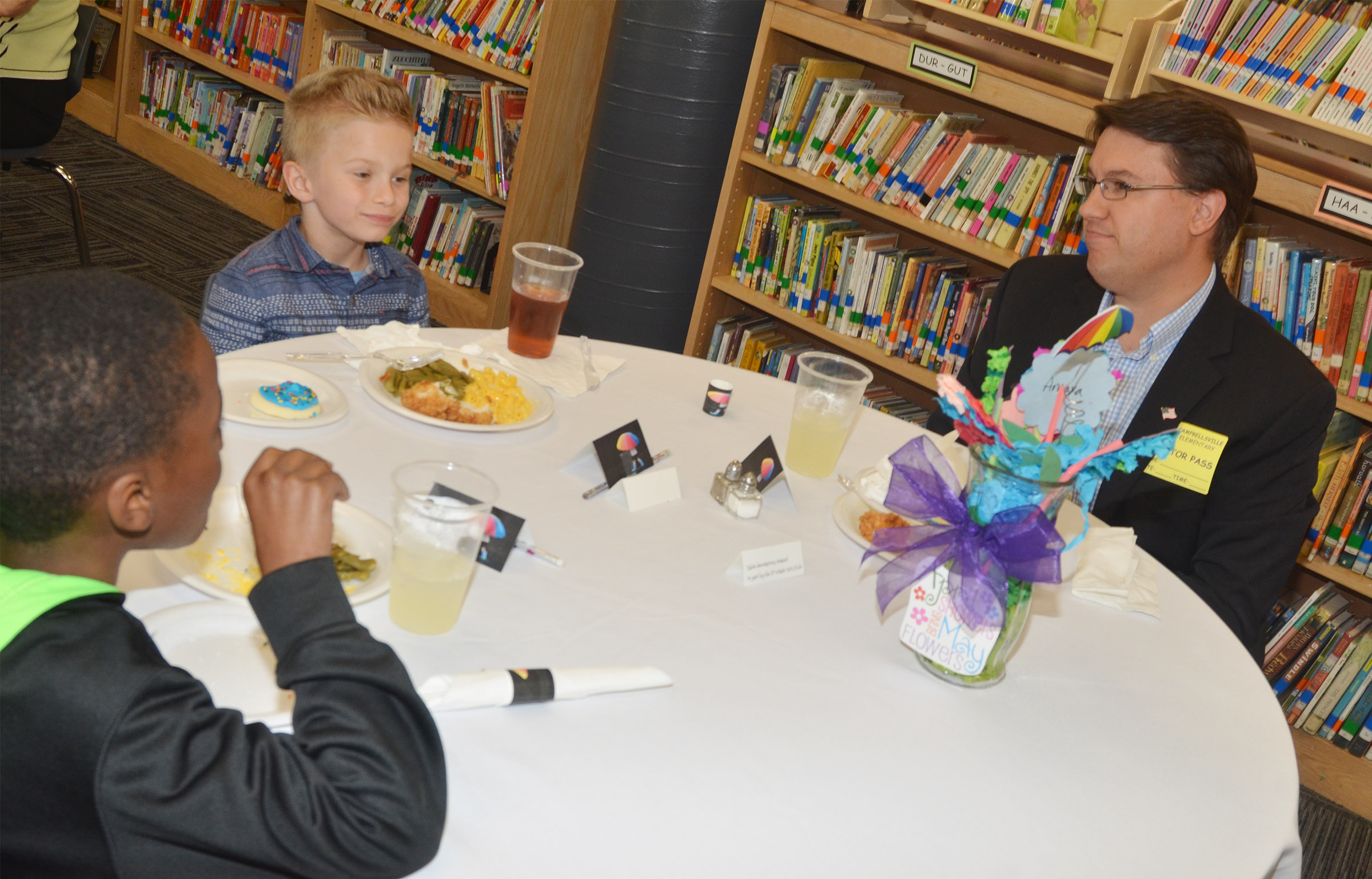 Dave DeBrot, financial advisor at Edward Jones, has lunch with CES third-grader John Gholston, at left, and first-grader Parker Hamilton.