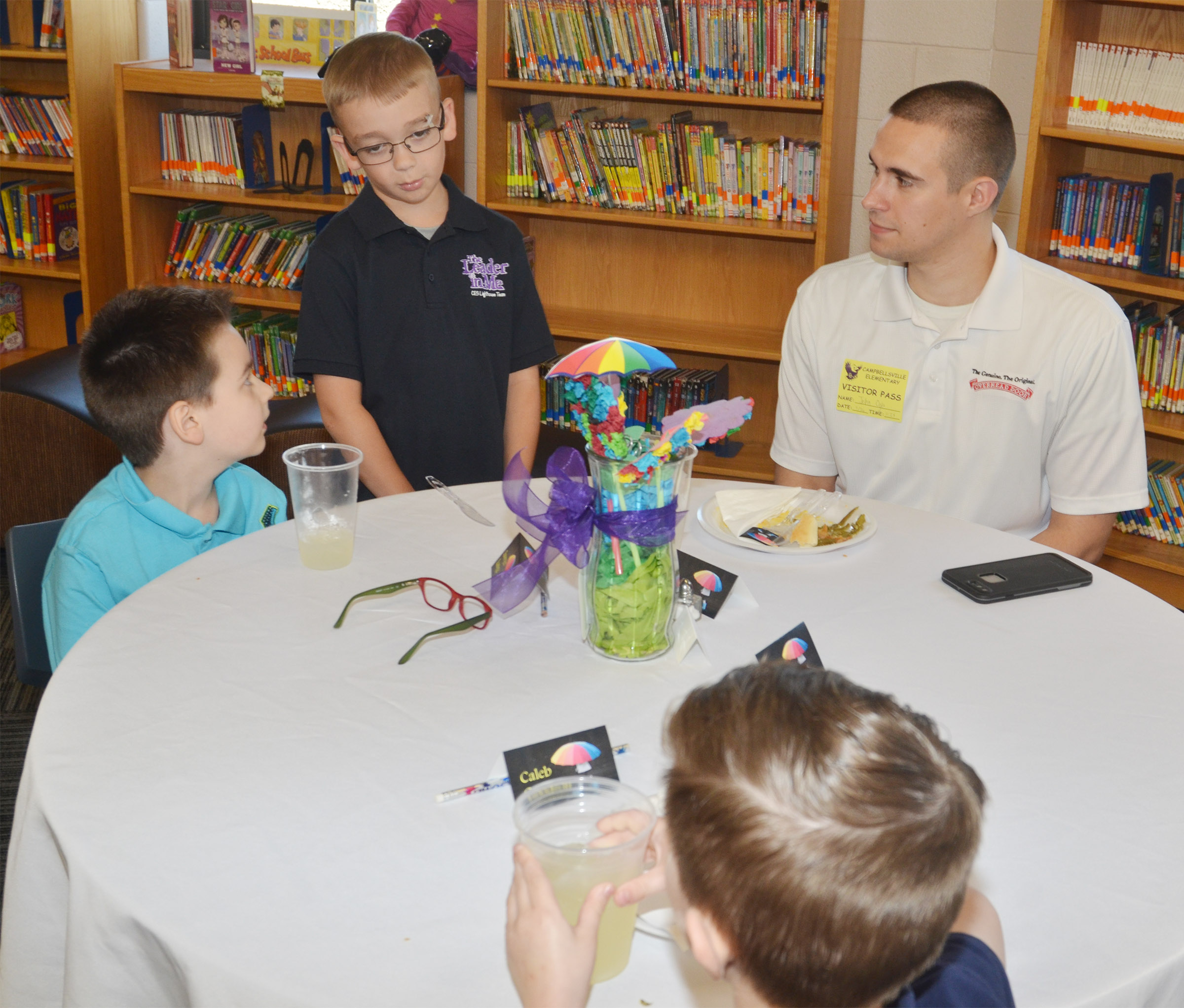 John Ogle, assistant operations manager at Overhead Door Co., talks with CES first-grader Sawyer Lange, far left, and kindergartener Caleb Goodson as third-grader Cameron Estes asks those at the table if they would like dessert.