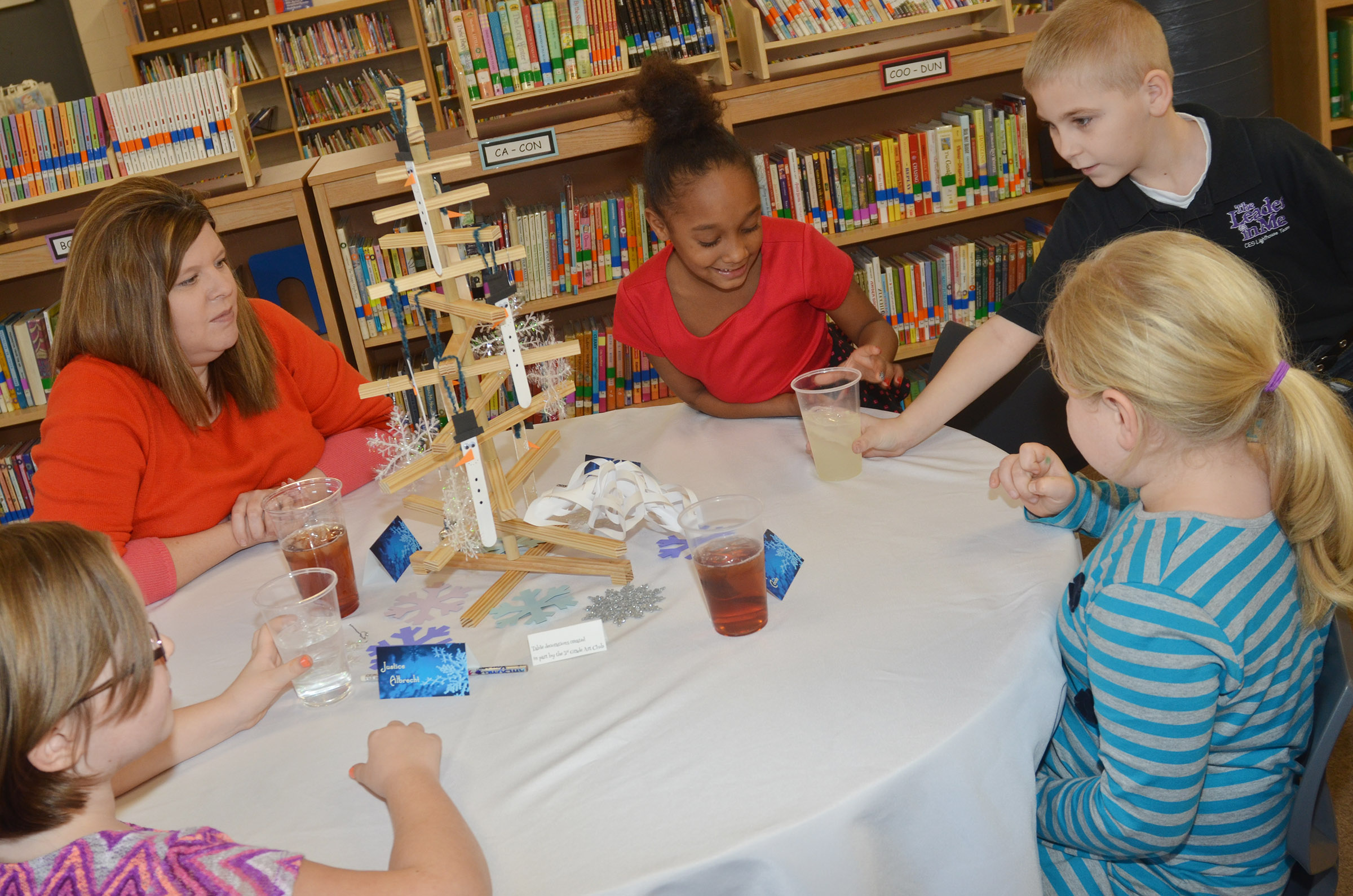 CES second-grader Joseph Greer, who is a member of his school's Lighthouse Team, serves second-grader Lashonda Wilkinson a glass of lemonade. Wilkinson and her classmates had lunch with Campbellsville Independent Schools Payroll Clerk/Insurance Coordinator Rebecca Tungate, at left.