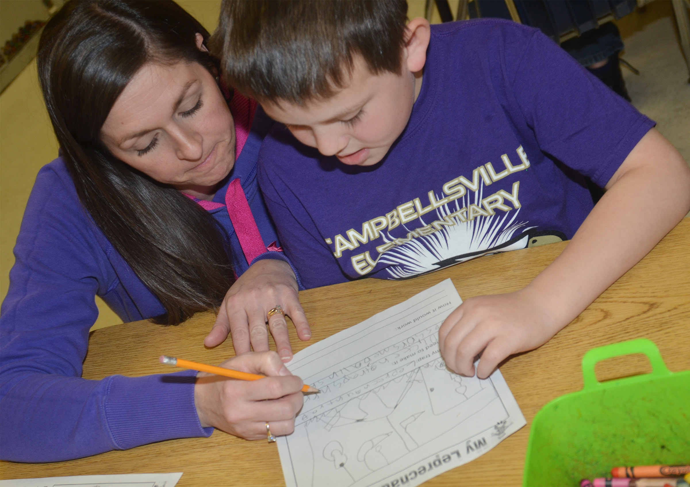 CES art teacher Adrienne Hash helps first-grader Atticus Strange write about his leprechaun trap.
