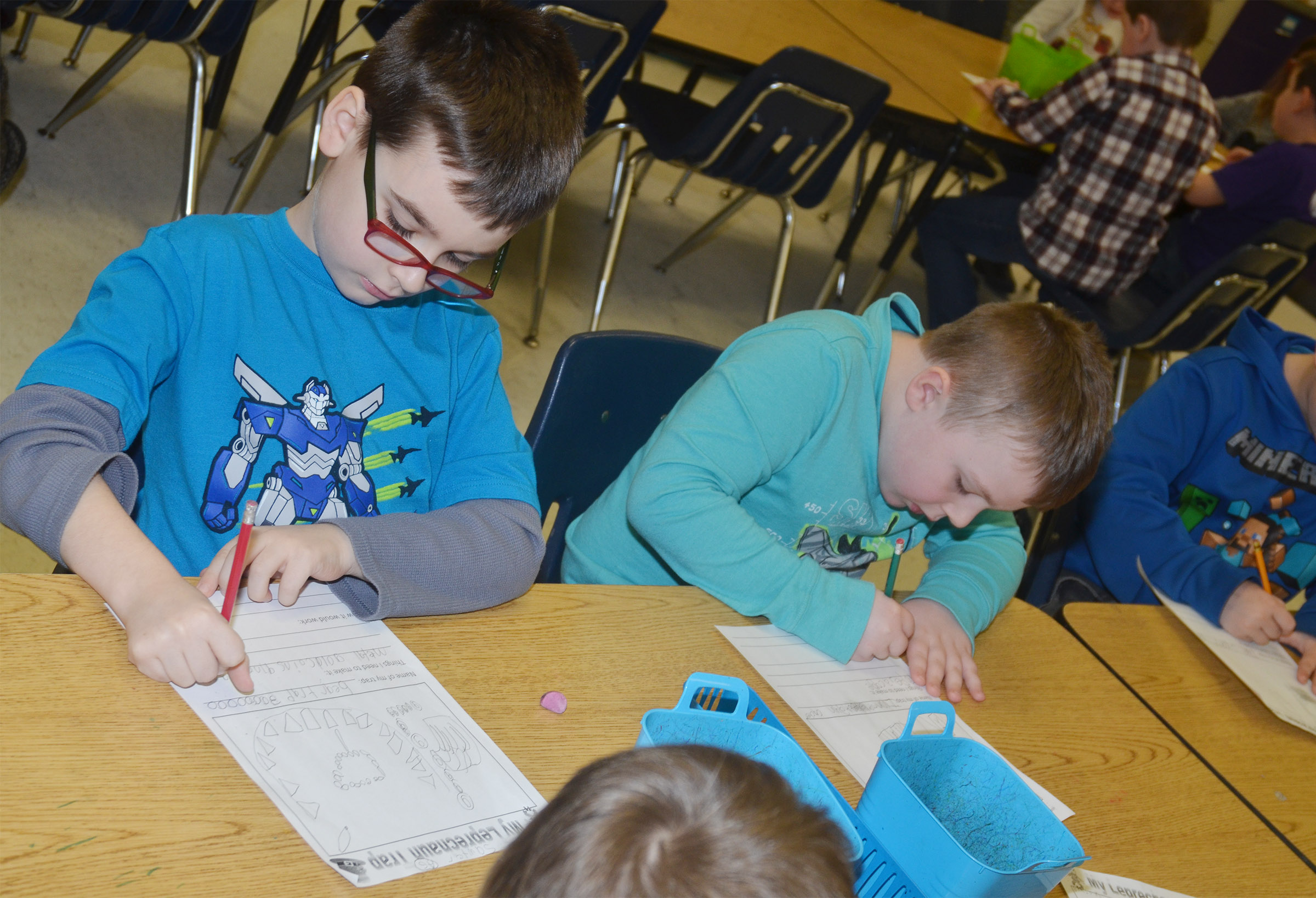 CES first-graders Sawyer Lange, at left, and Hunter Clark write about their leprechaun traps.