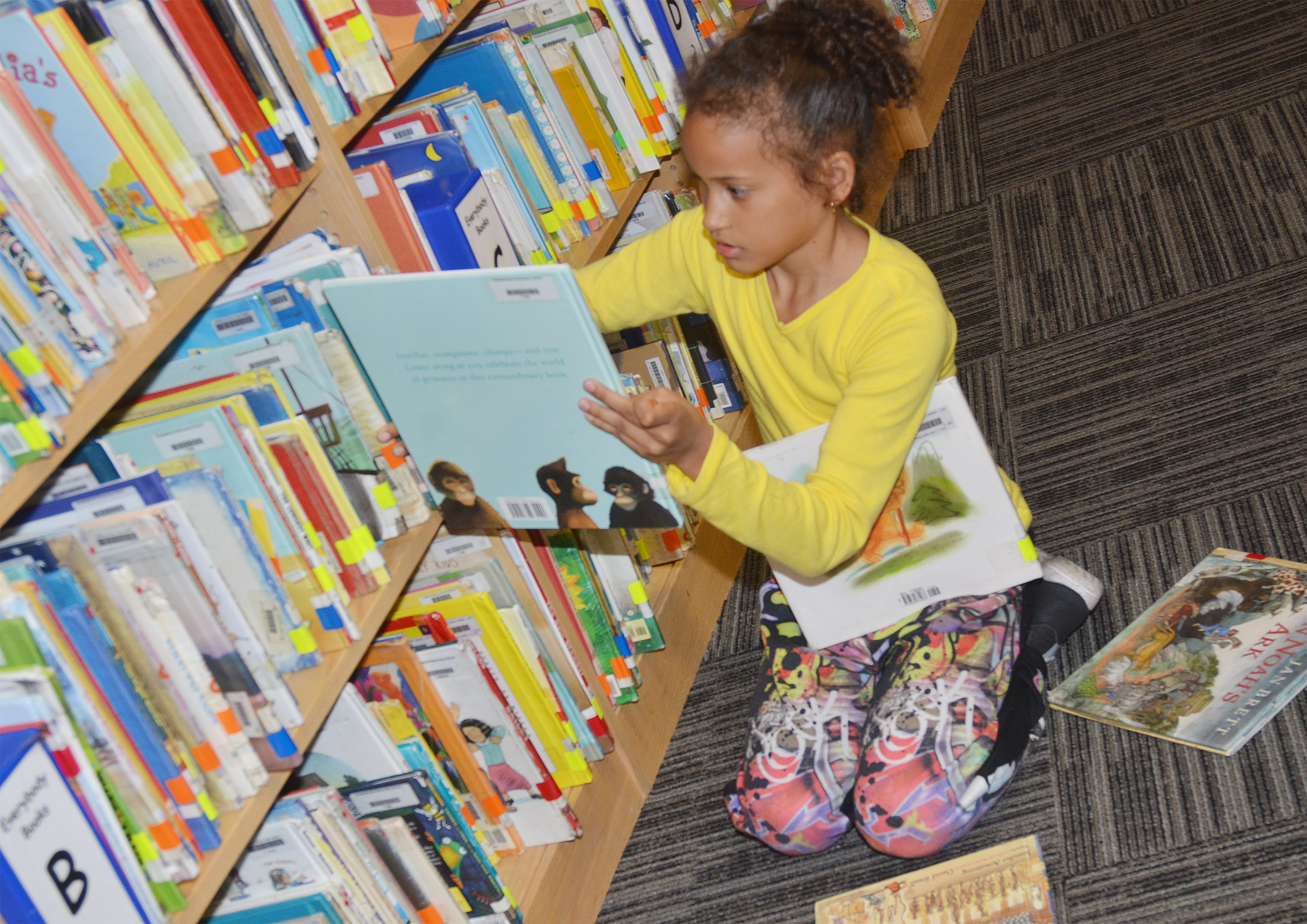 CES second-grader Yazlyn Sutton looks for a book to check out.