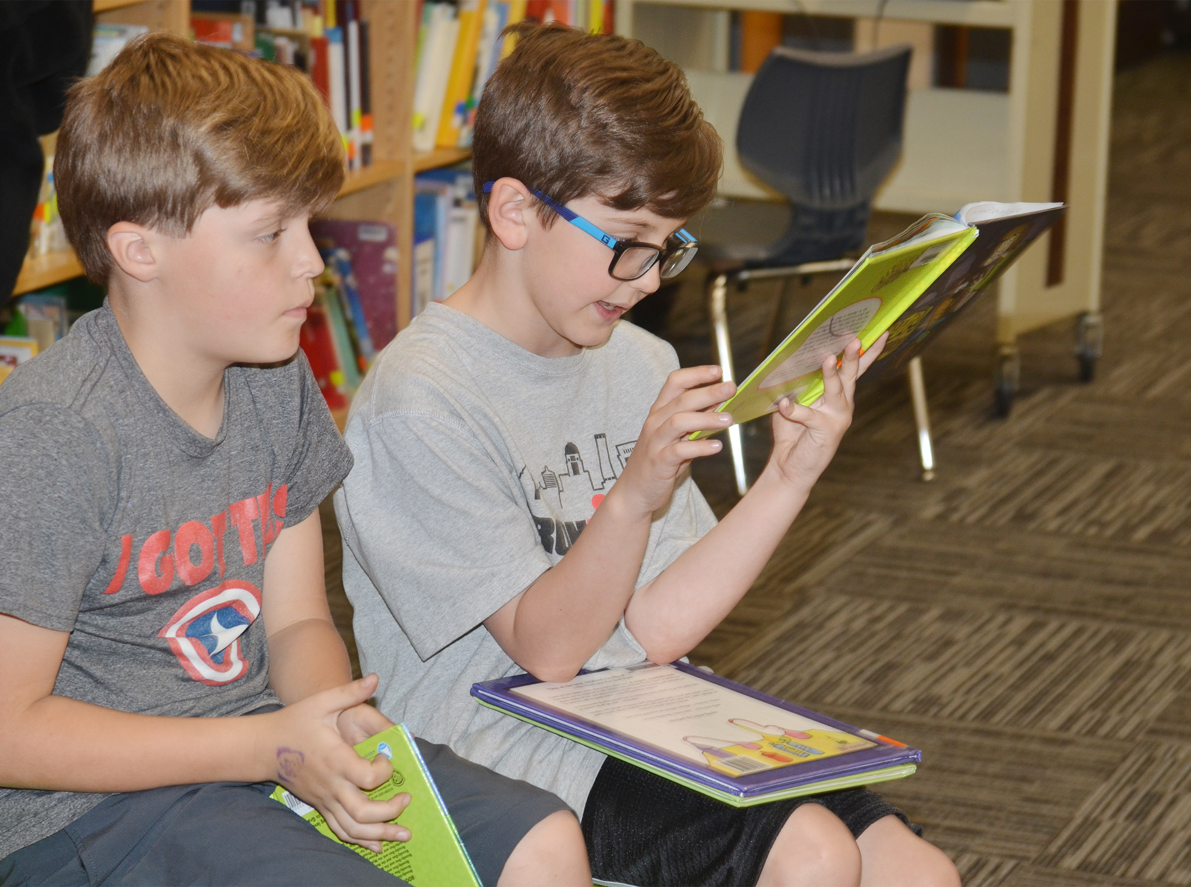 CES second-grader Tye Rhodes reads to classmate Emerson Gowin.