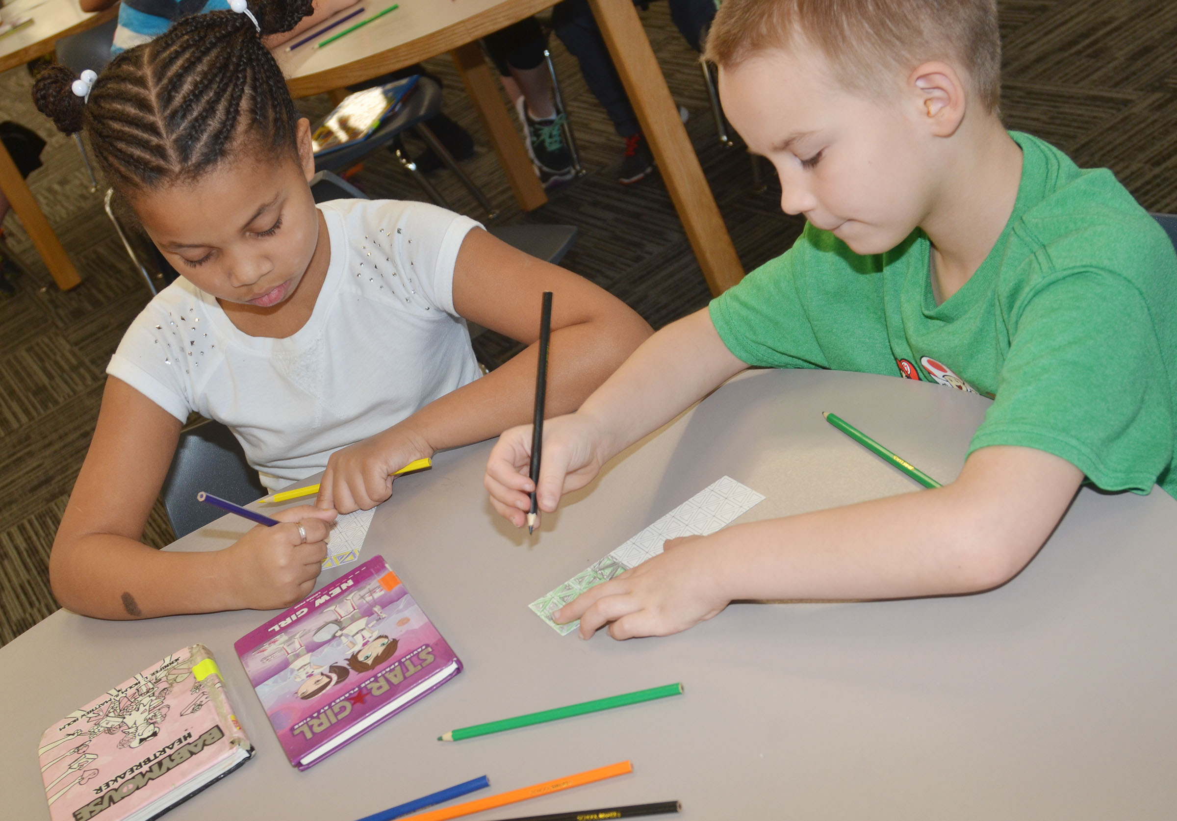 CES first-graders Journey Webb, at left, and Jackson Bates color bookmarks at the library.
